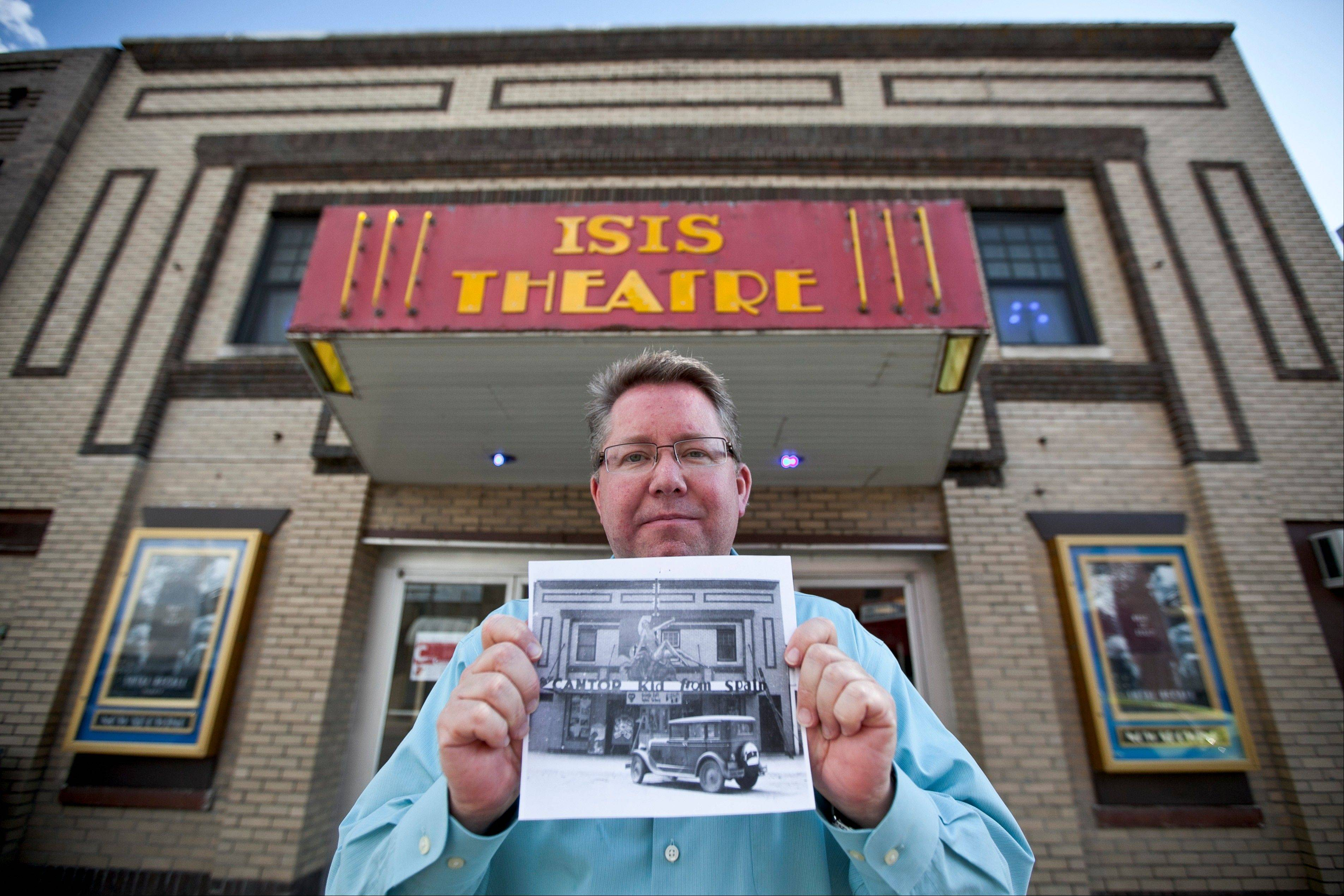 "Thom Reeves, owner of the Isis theater, holds a photo showing the building's facade in 1932 during the showing of the movie ""The Kid from Spain"", starring Eddie Cantor, in Crete, Neb."