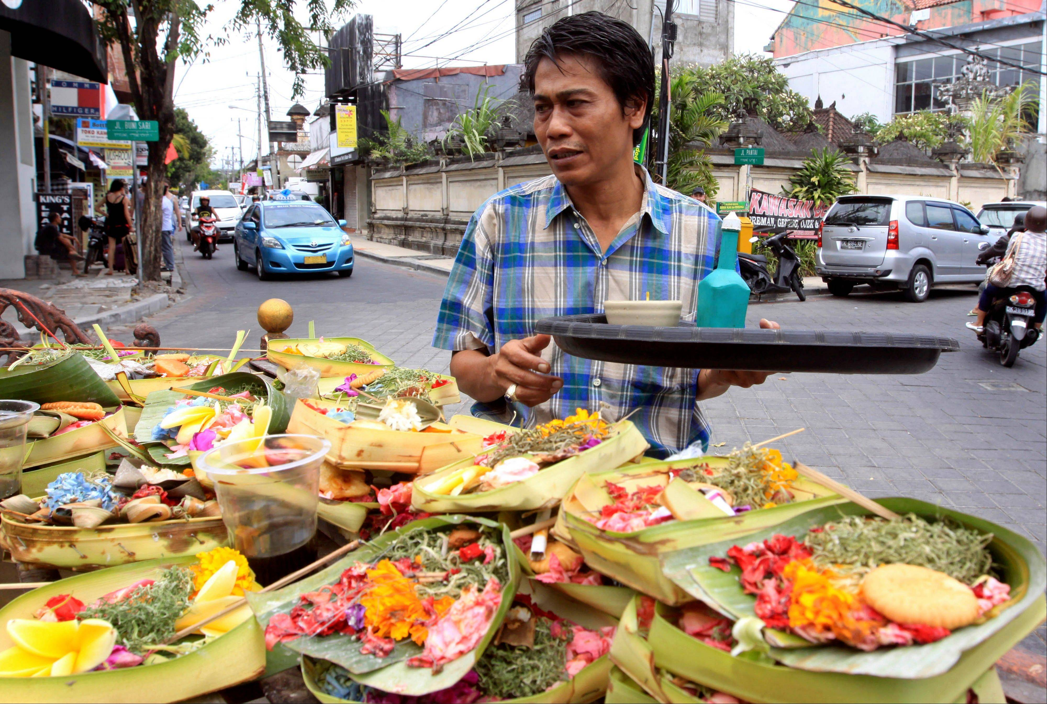 A Balinese man offers food to a local god in Kuta, Bali, Indonesia. It can be hard to find Bali's serenity and beauty amid the villas with infinity pools and ads for Italian restaurants.