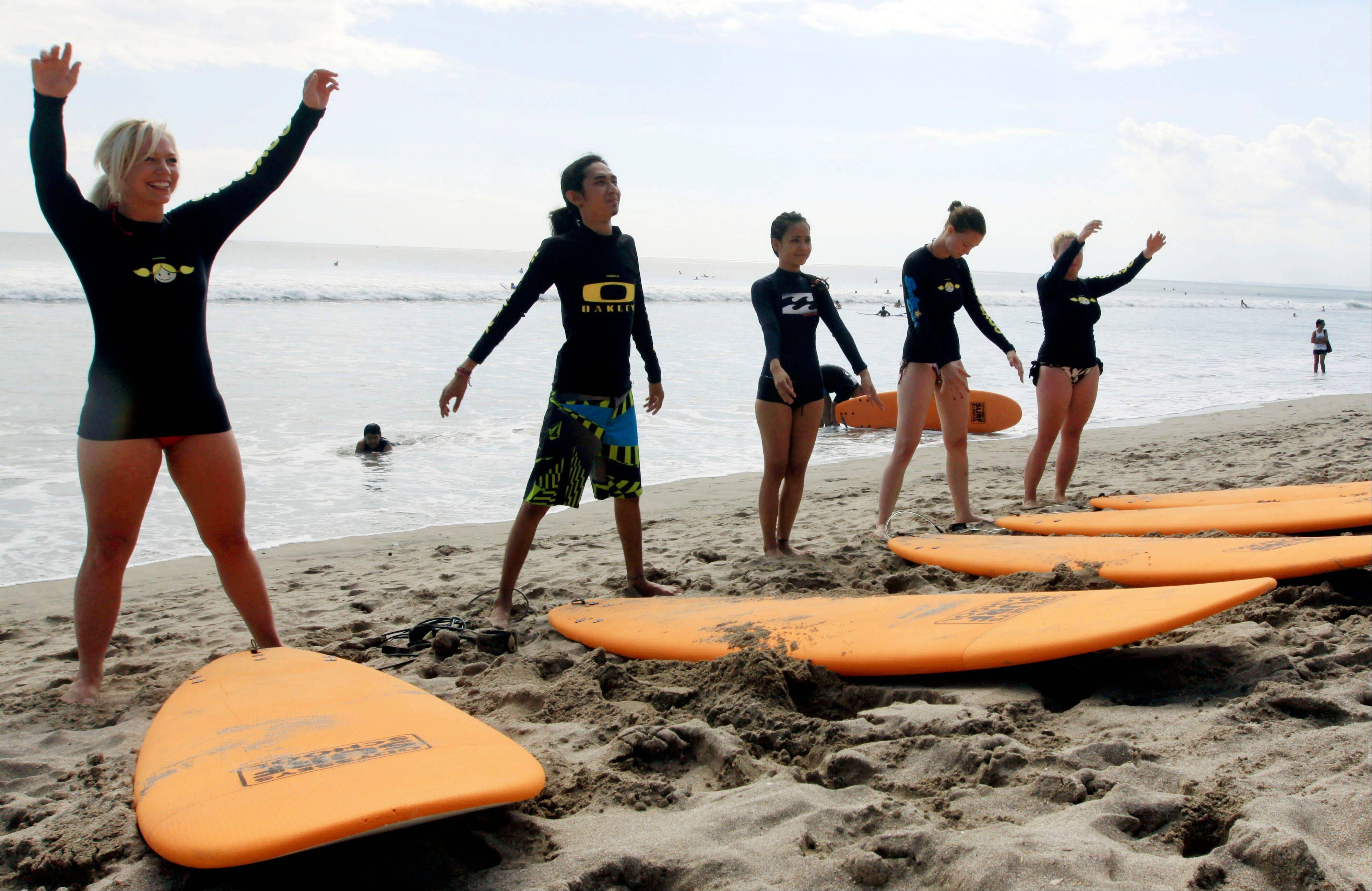 Tourists take surfing lessons on Kuta beach.