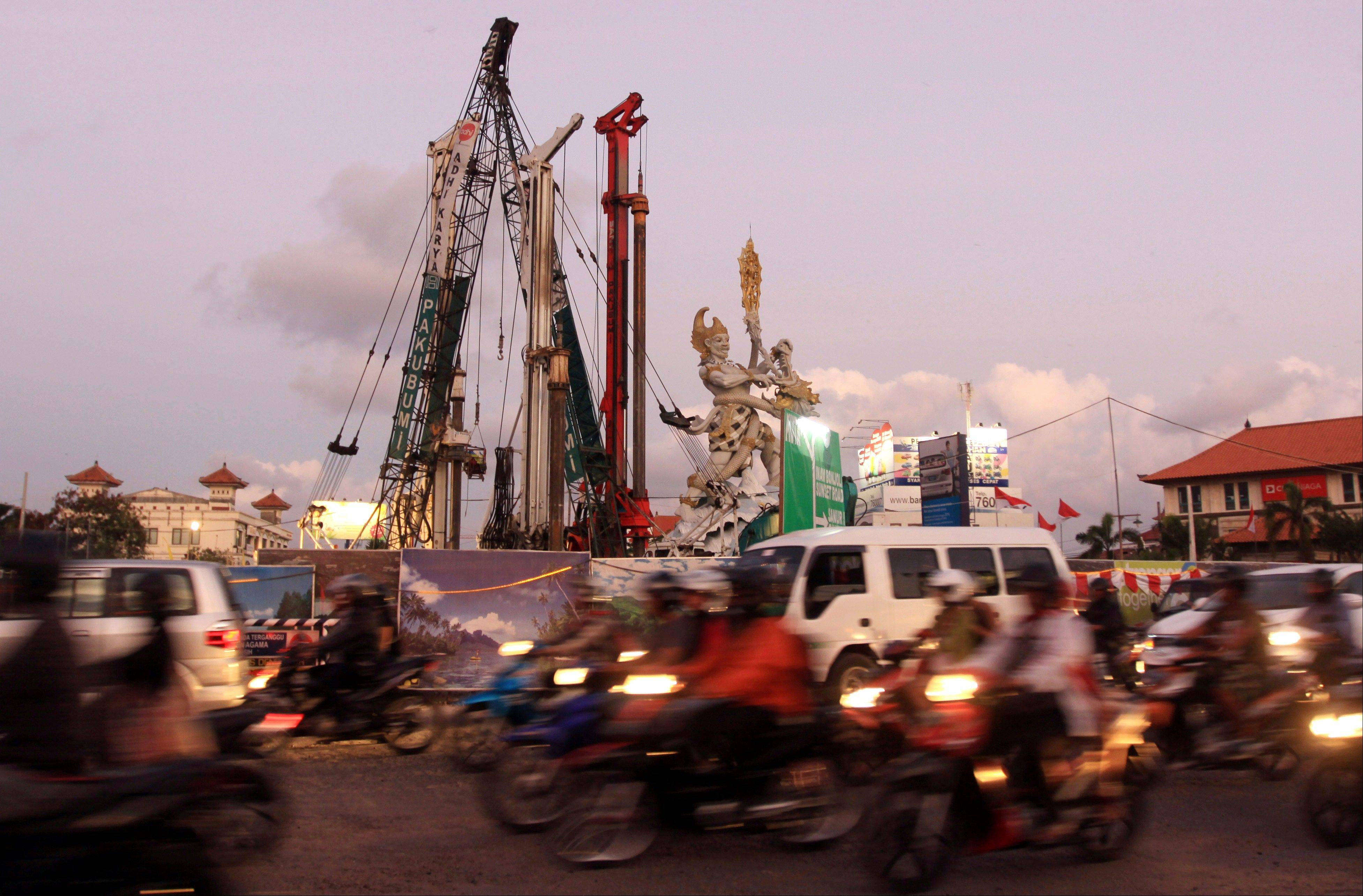 Cranes work next to a traditional Balinese statue called Dewa Ruci at the site of road construction in Kuta Bali.