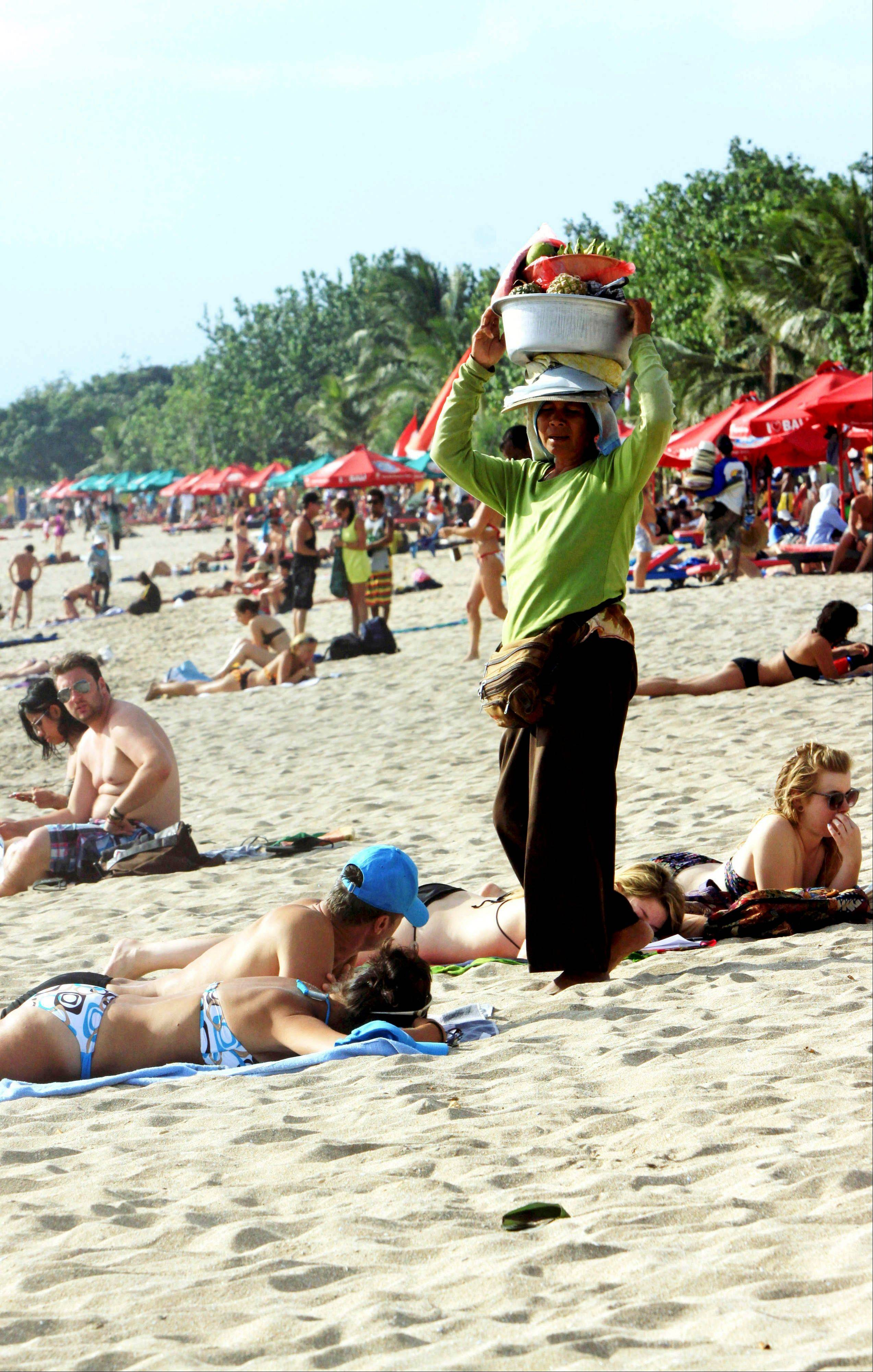 A Balinese vendor sells fruit to tourists on Kuta beach.