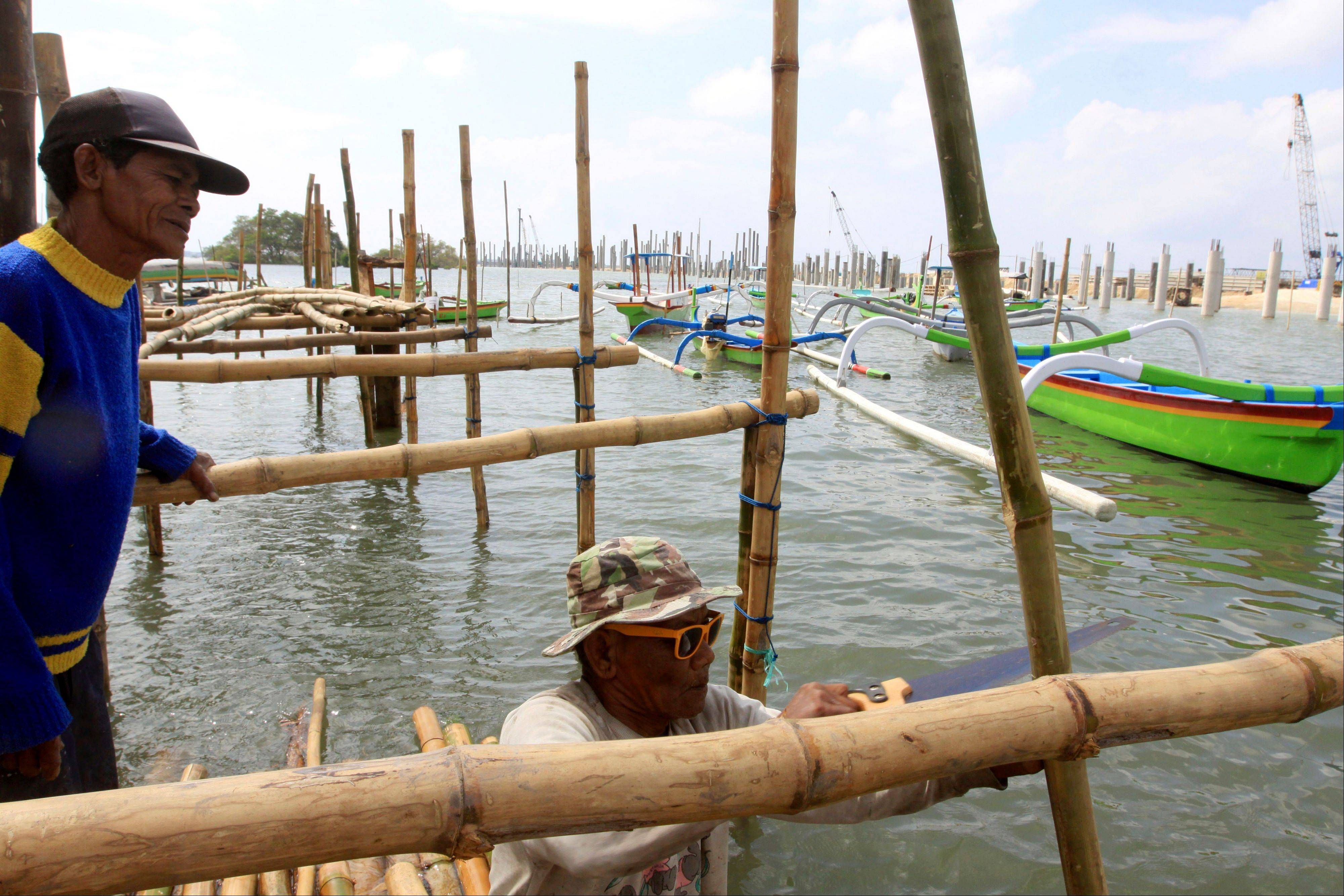 Balinese men build a bamboo bridge next to a road construction site in Kuta, Bali.