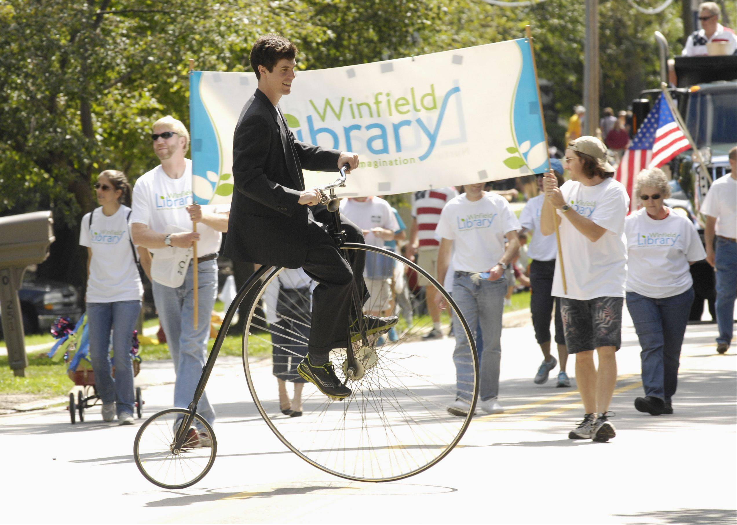 Brendan Wischweh, a teacher in Naperville, rides his big wheel bike with the Winfield Library group marching in Winfield's Good Old Day festival parade Sunday.