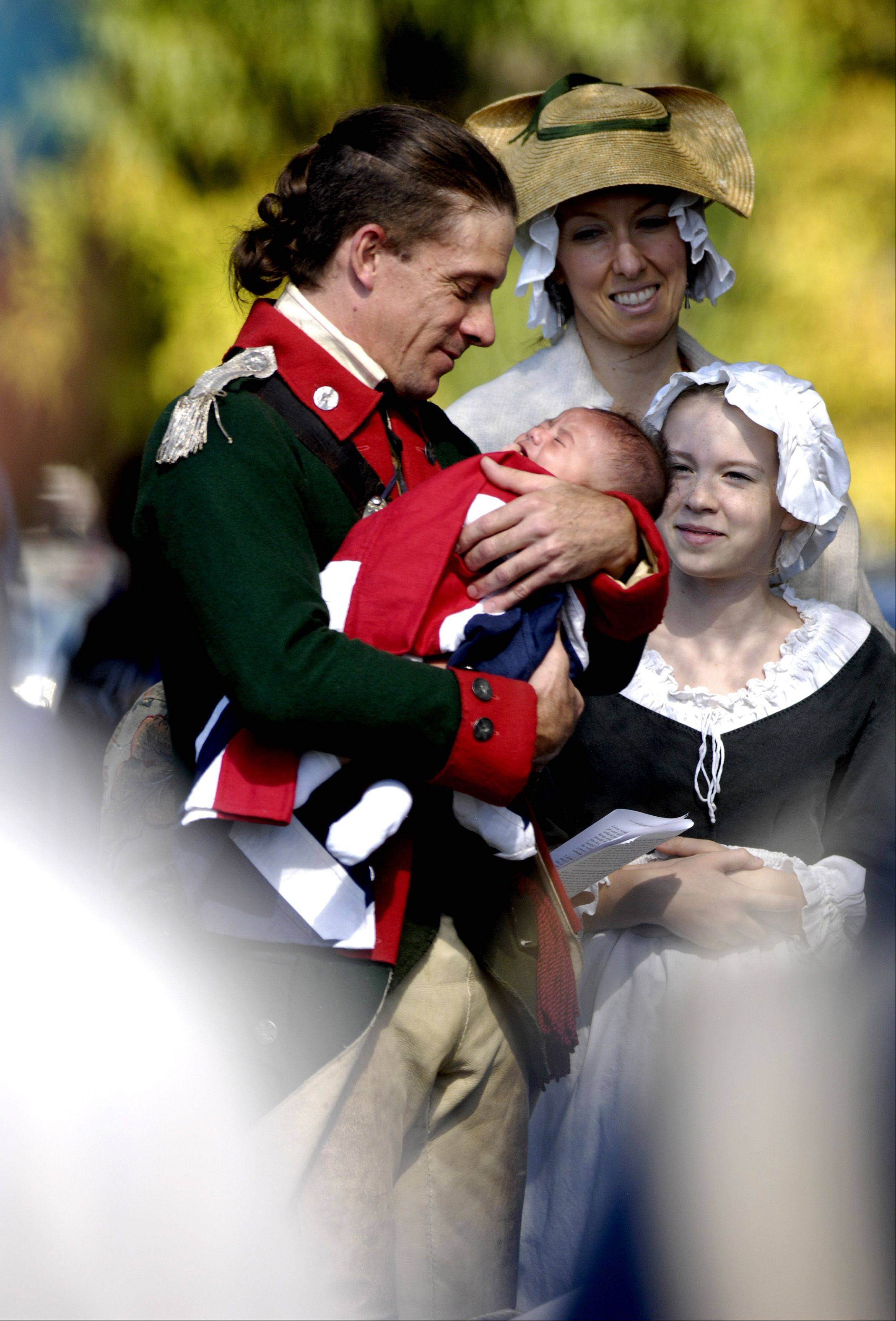 Re-enactor Tim Hess, of Streamwood, holds his newly baptized son, Ian, wrapped in a British flag, during a real baptism ceremony before a Revolutionary War battle re-enactment Sunday at Cantigny Park in Wheaton.