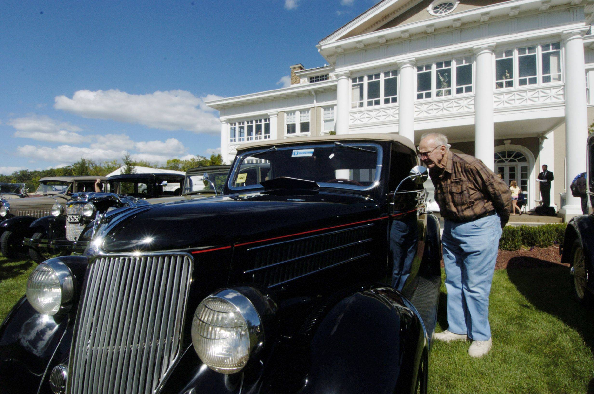 Ron Waltz, of Lake Villa, takes a peek inside a 1936 Ford on display during the 100th anniversary celebration of the Lehmann Mansion in Lake Villa Sunday.