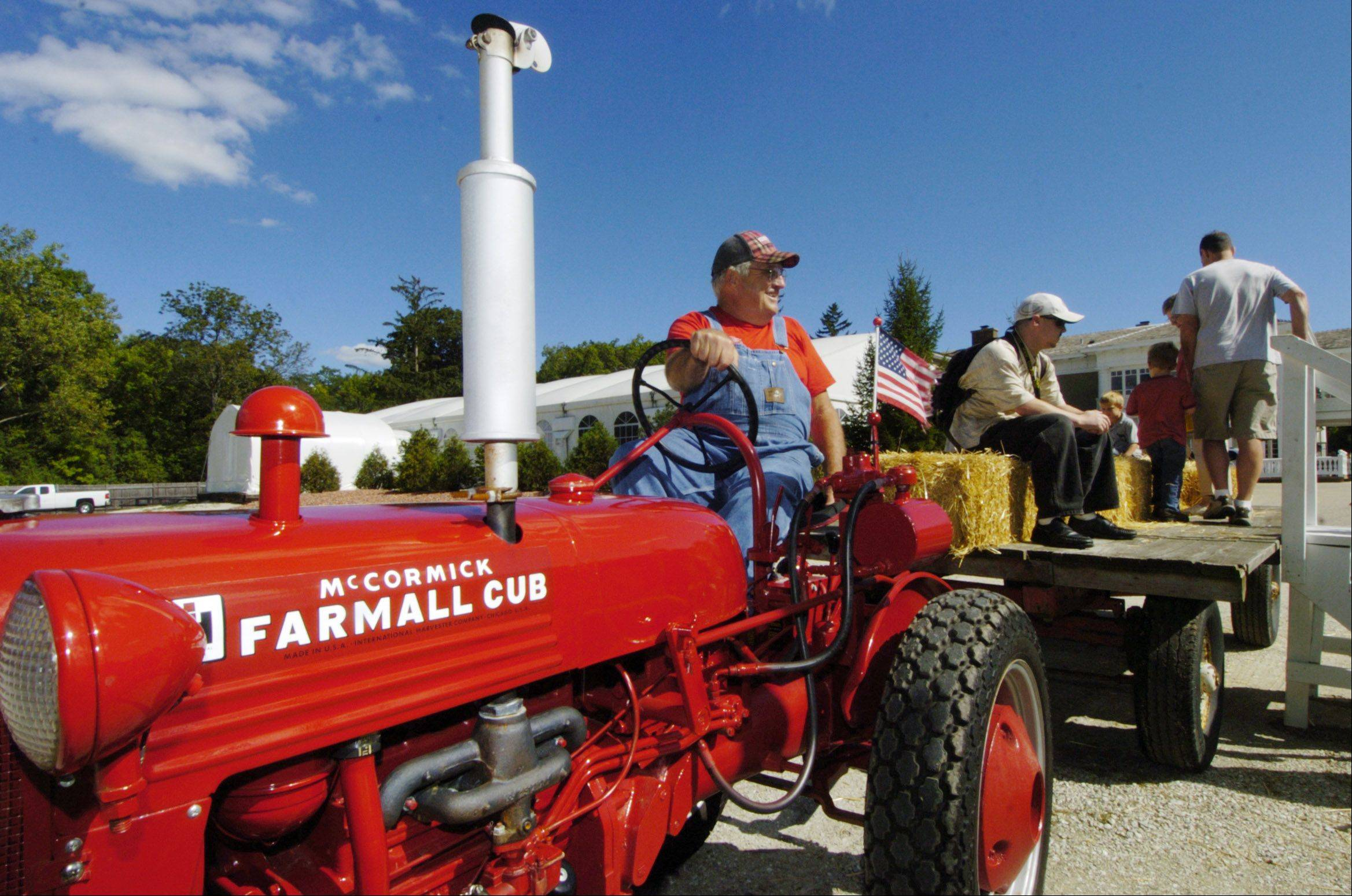 JOE LEWNARD/jlewnard@dailyherald.comBobby Carlson, of Arlington Heights, boards passengers for a hay ride being pulled by his 1949 International Cub tractor during the 100th anniversary celebration of the Lehmann Mansion in Lake Villa Sunday.