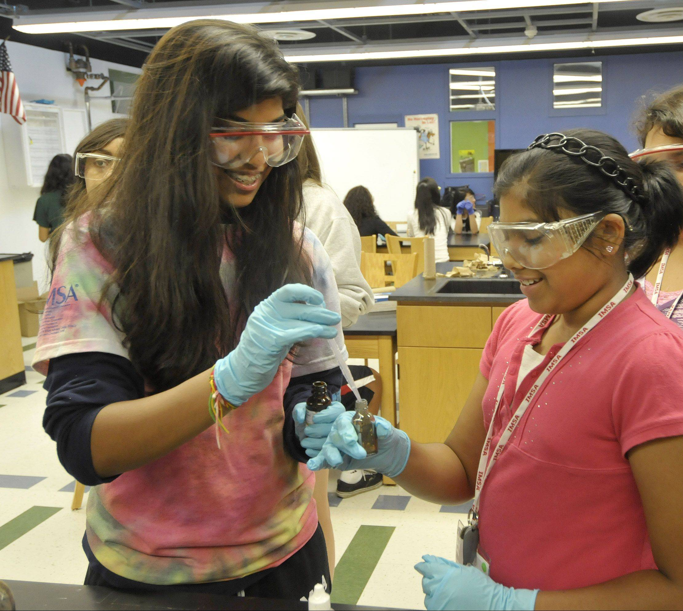 Illinois Mathematics and Science Academy student volunteer Sai Talluru of Aurora mixes two chemicals in a bottle for Science@IMSA camp student Isha Tyle. As the civil rights law Title IX turned 40, some say ensuring gender equality in science, technology, engineering and math education will become the next focus.