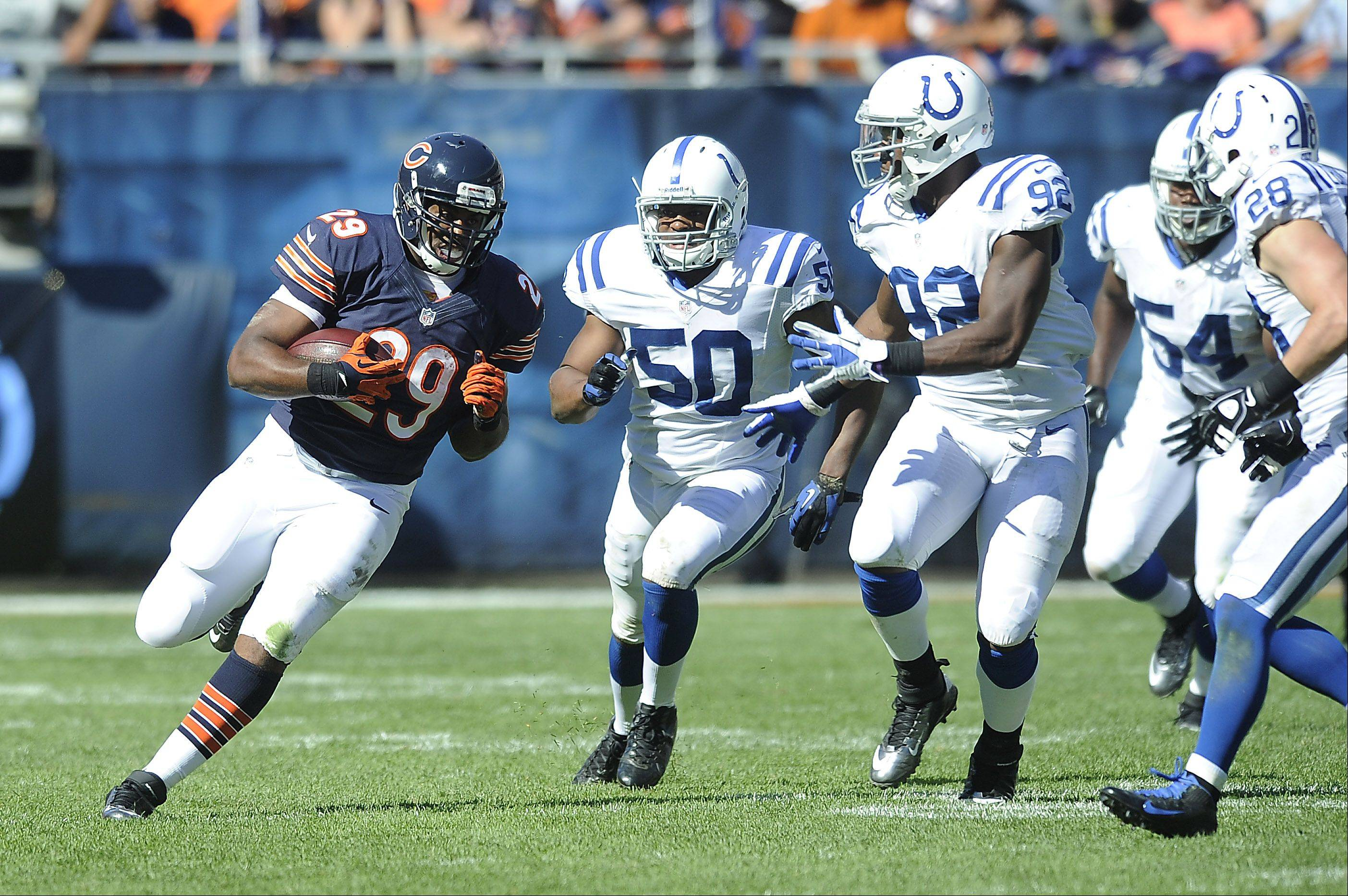 Chicago Bears Michael Bush runs for yardage in the 4th quarter despite pressure from the Colts defense in the Bears home opener at Soldier Field in Chicago.