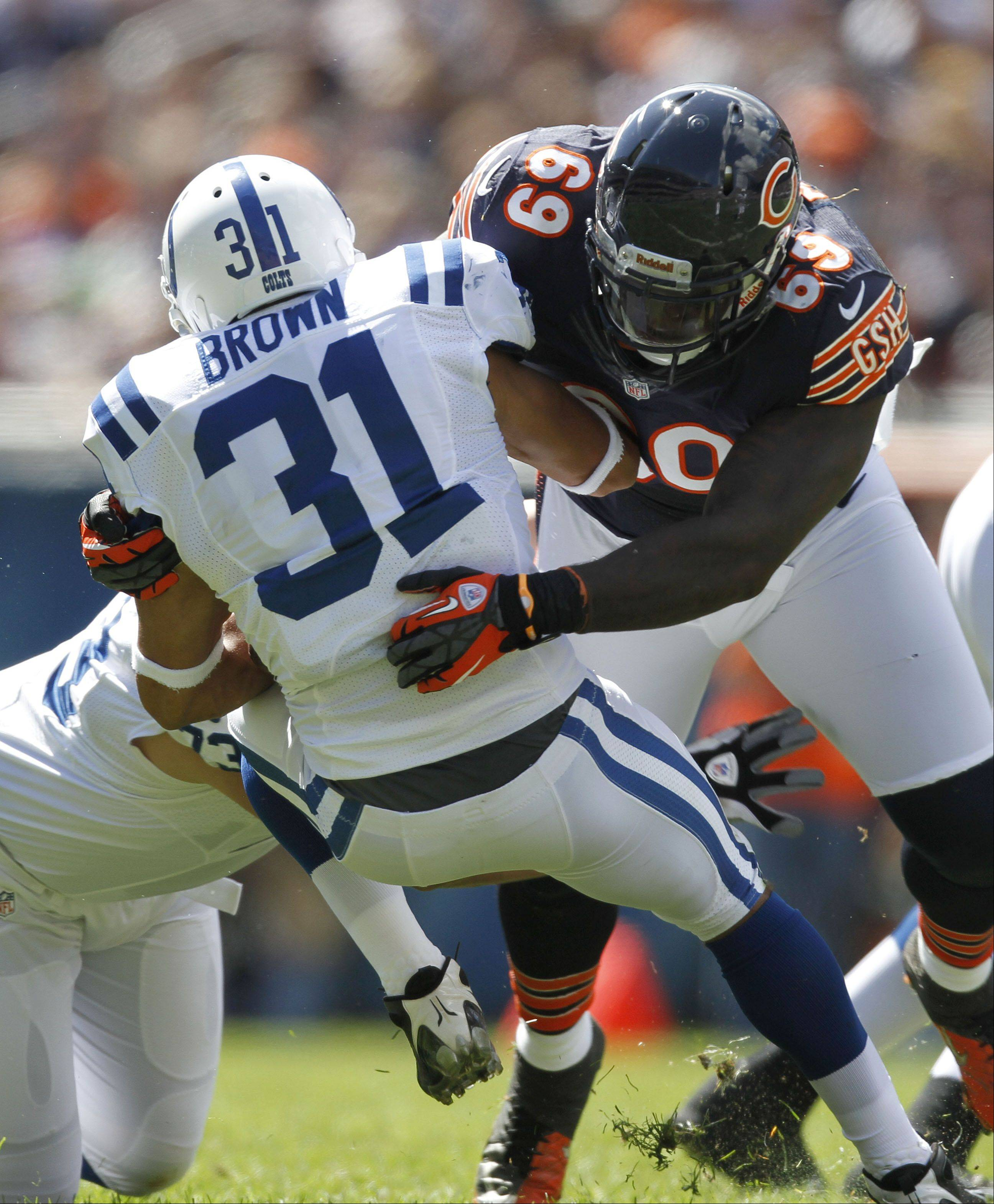 Chicago Bears defensive end Henry Melton hits Indianapolis Colts running back Donald Brown for a loss during the Bears season opener.