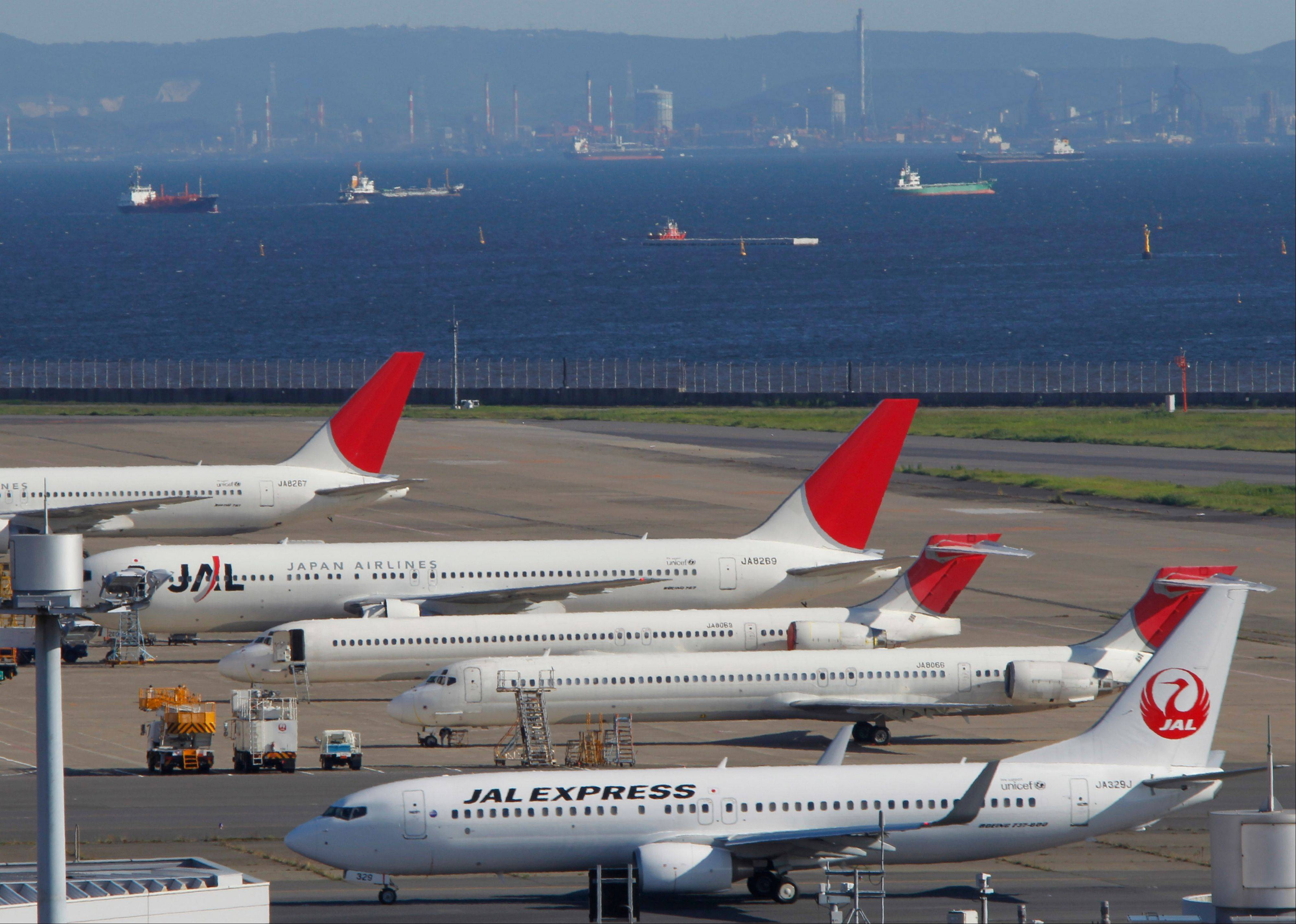 Japan Airlines passenger planes park on the tarmac of Tokyo's Haneda Airport in Tokyo Monday, Sept. 10, 2012. Japan Airlines Co. is raising 663 billion yen ($8.5 billion) in its initial public offering, pricing its shares at the top of its range at 3,790 yen ($48) ó the world's second biggest IPO this year after Facebook.