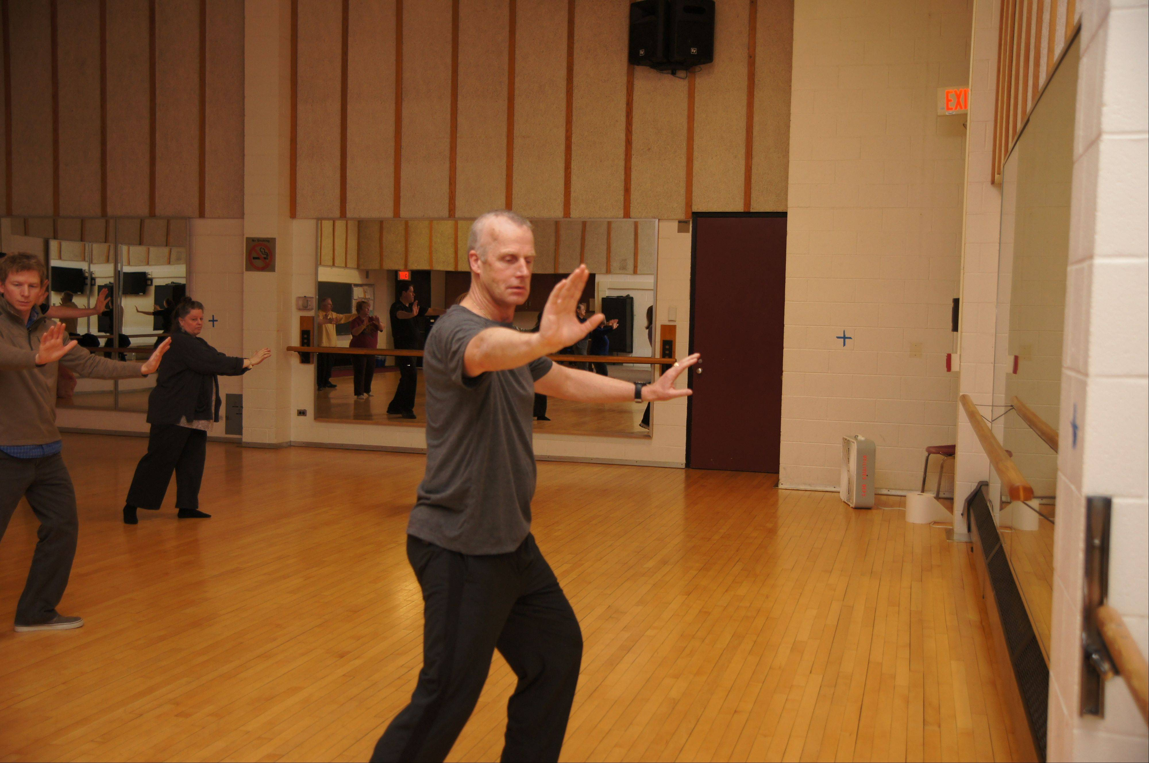 "Scott Garske, his hands spread as part of a ""single whip"" step, teaches Sun (""soon"") style tai chi at Harper College in Palatine."