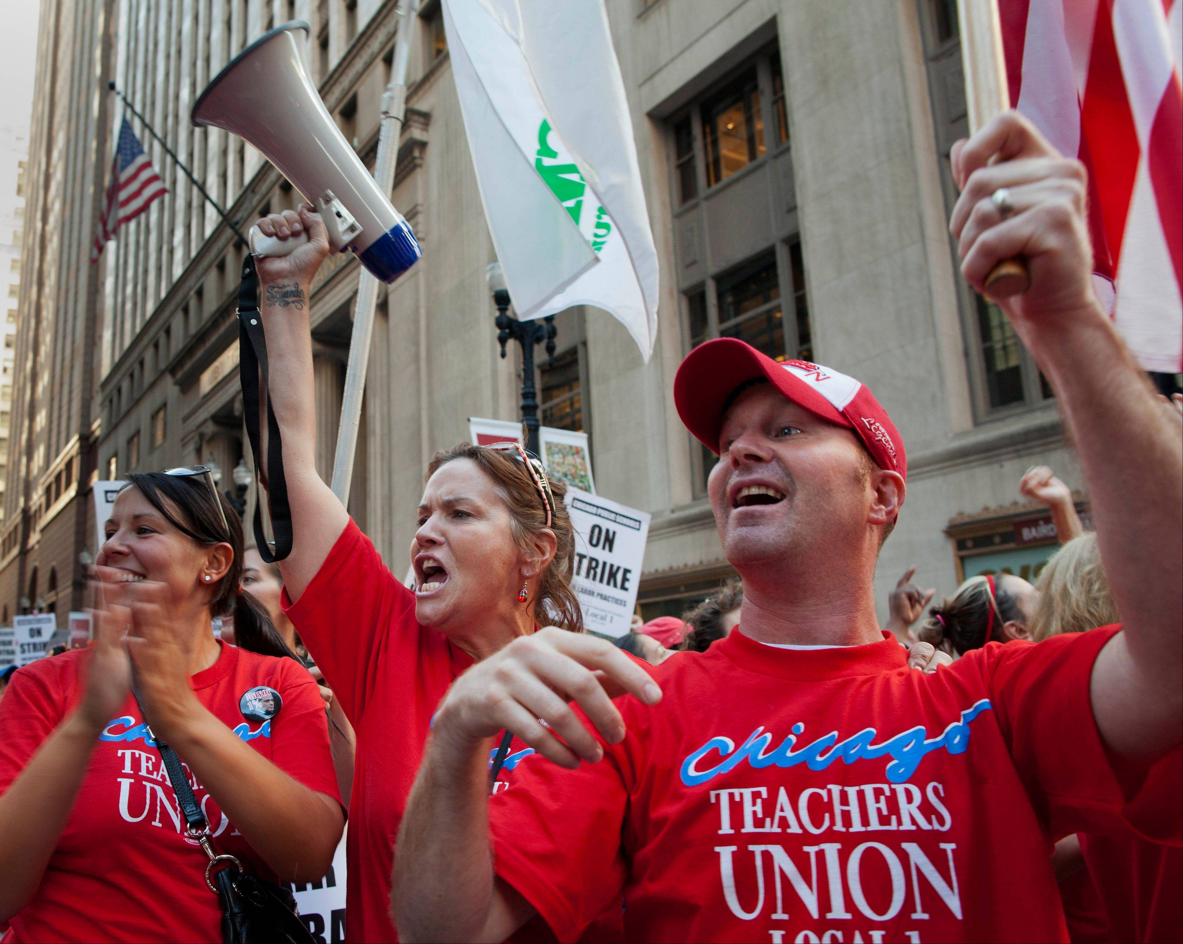 Teachers cheer as they march on streets surrounding the Chicago Public Schools district headquarters on Monday, the first day of their strike.