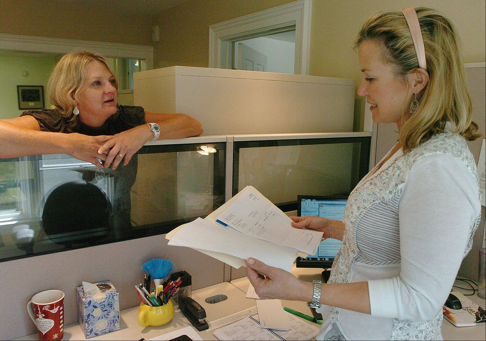 Janet VanZant of Deer Park, left, and Beth McAndrews of Barrington talk things over in the office at the Village of Deer Park. They found their jobs with the help of CareerPlace in Barrington.