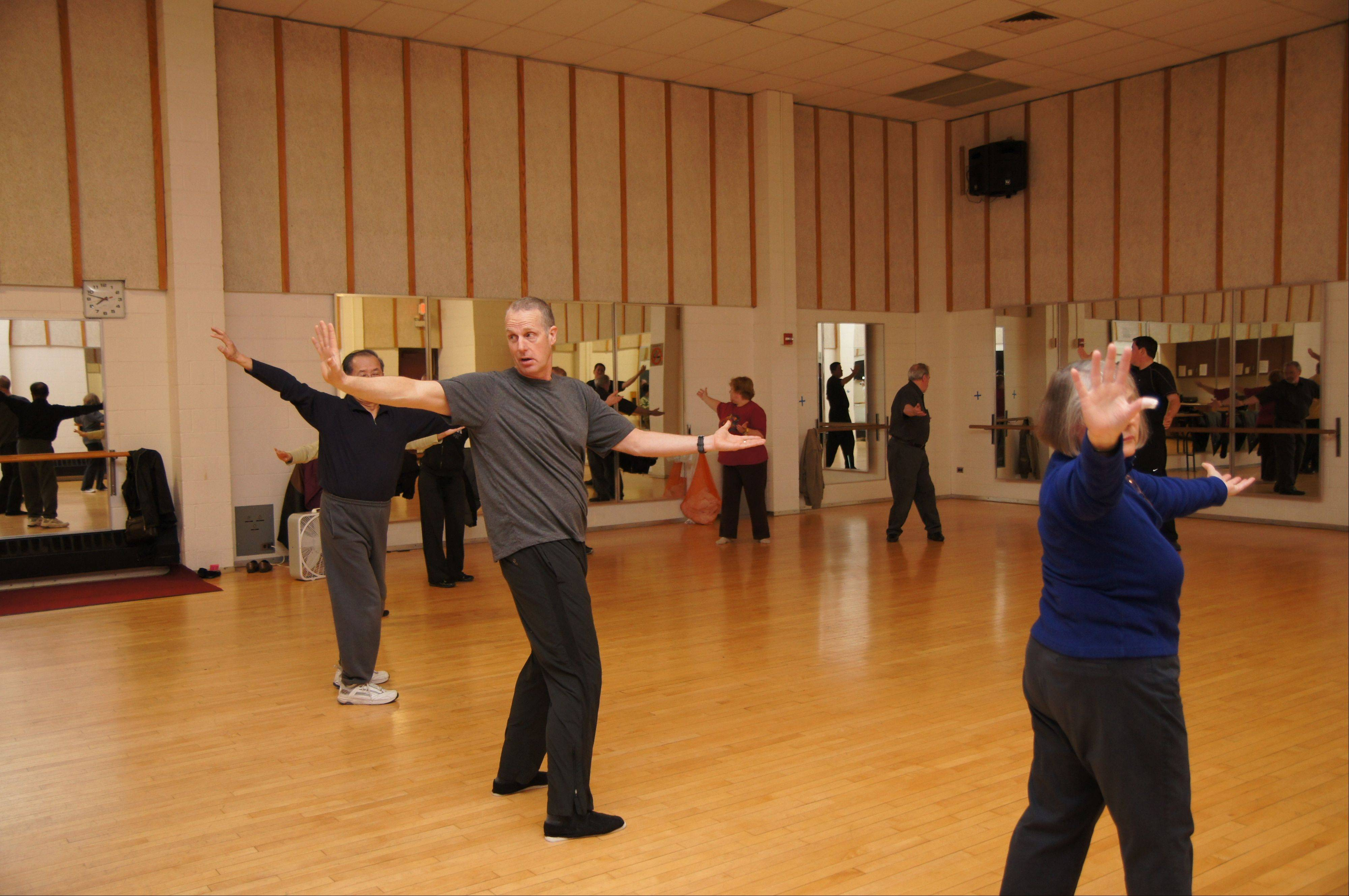 "Concentrating on the gap between his right thumb and index finger, Scott Garske leads a class in performing qi qong (""chi gung"") steps, a warm-up exercise."