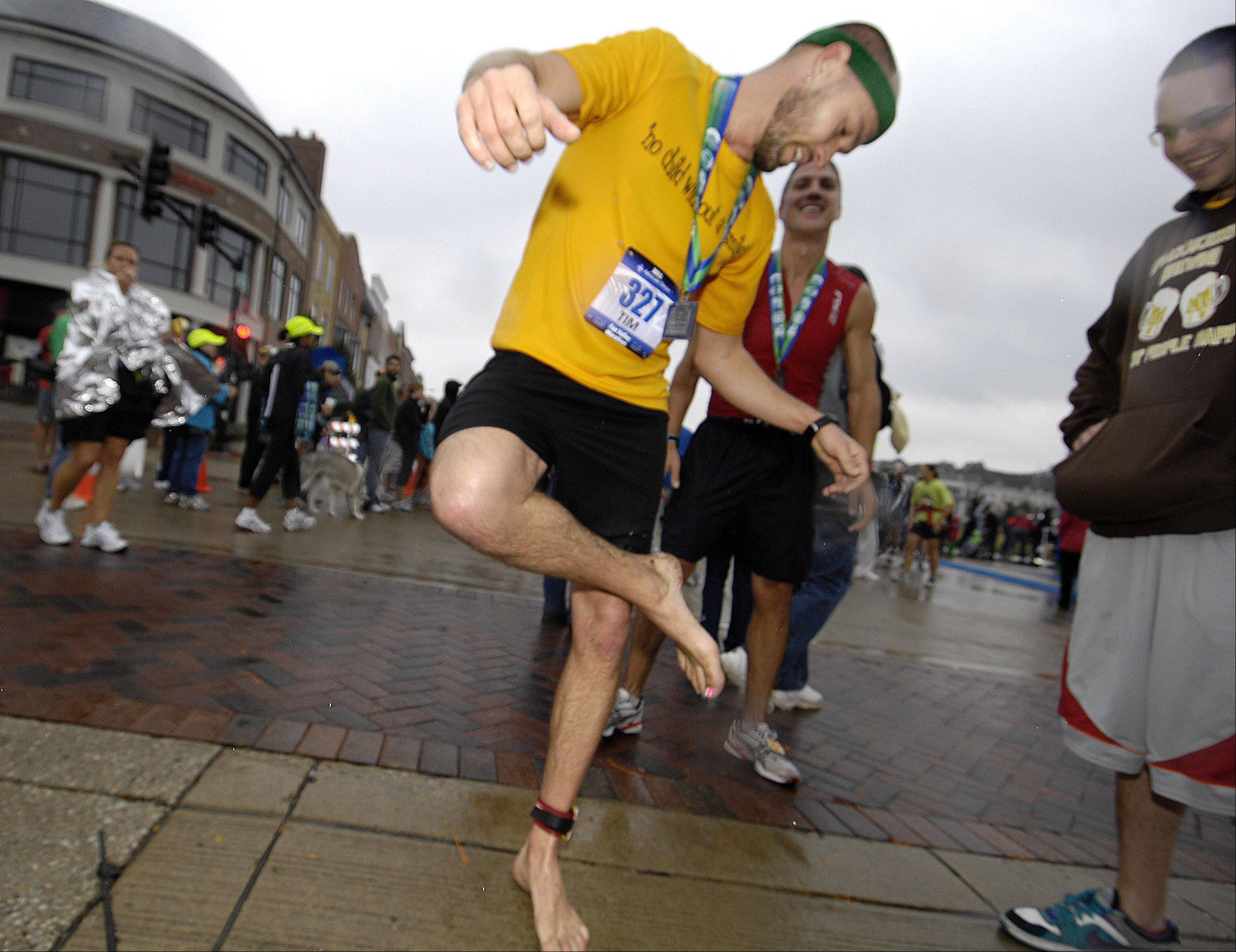 Tim Cunningham looks at the soles of his feet shortly after crossing the finish line to win last year's 26.2 mile Fox Valley Marathon. He ran the entire race without shoes. .