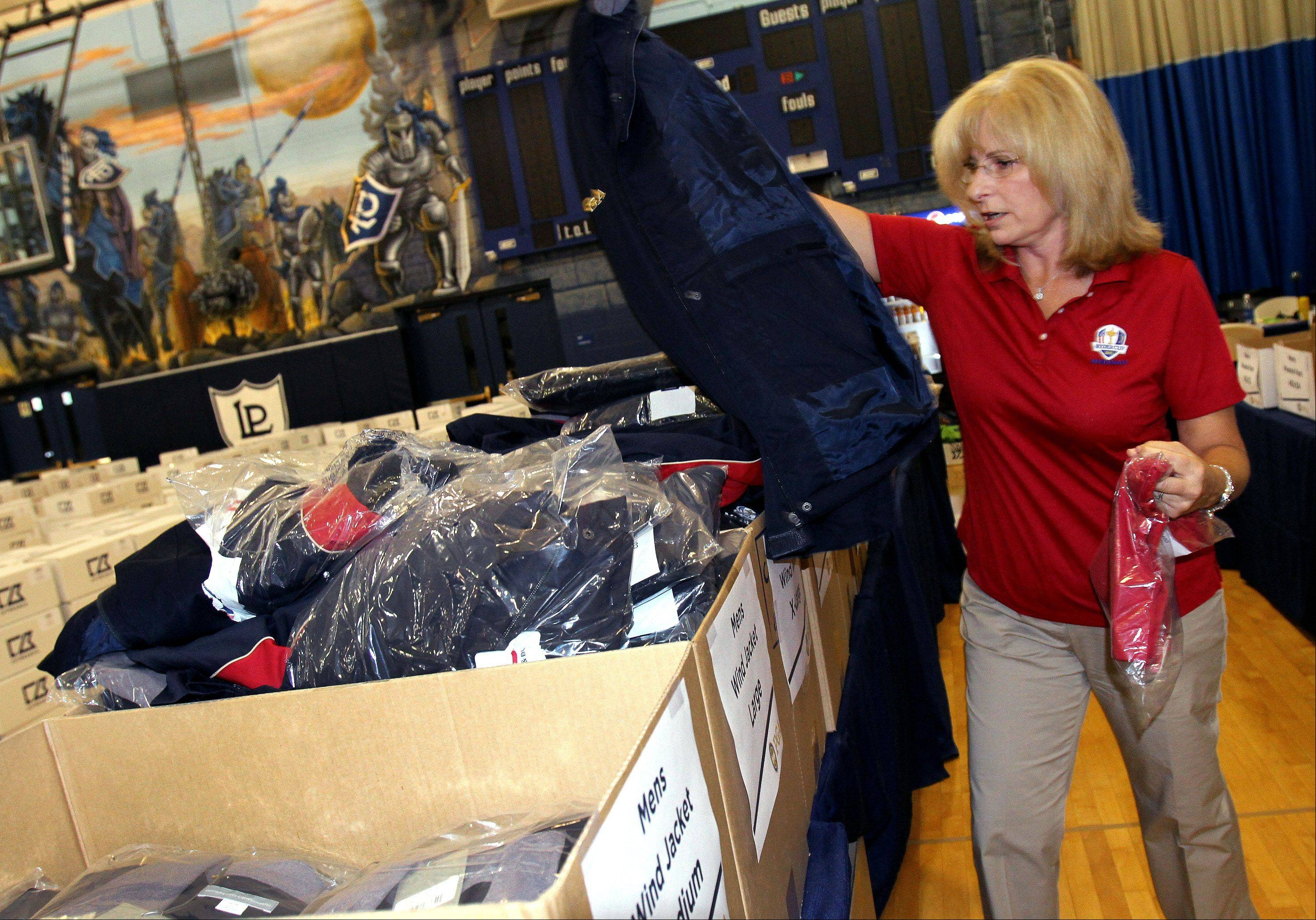 Volunteer Susan Novak of Mount Prospect gets another size jacket for working as a volunteer at the Ryder Cup.