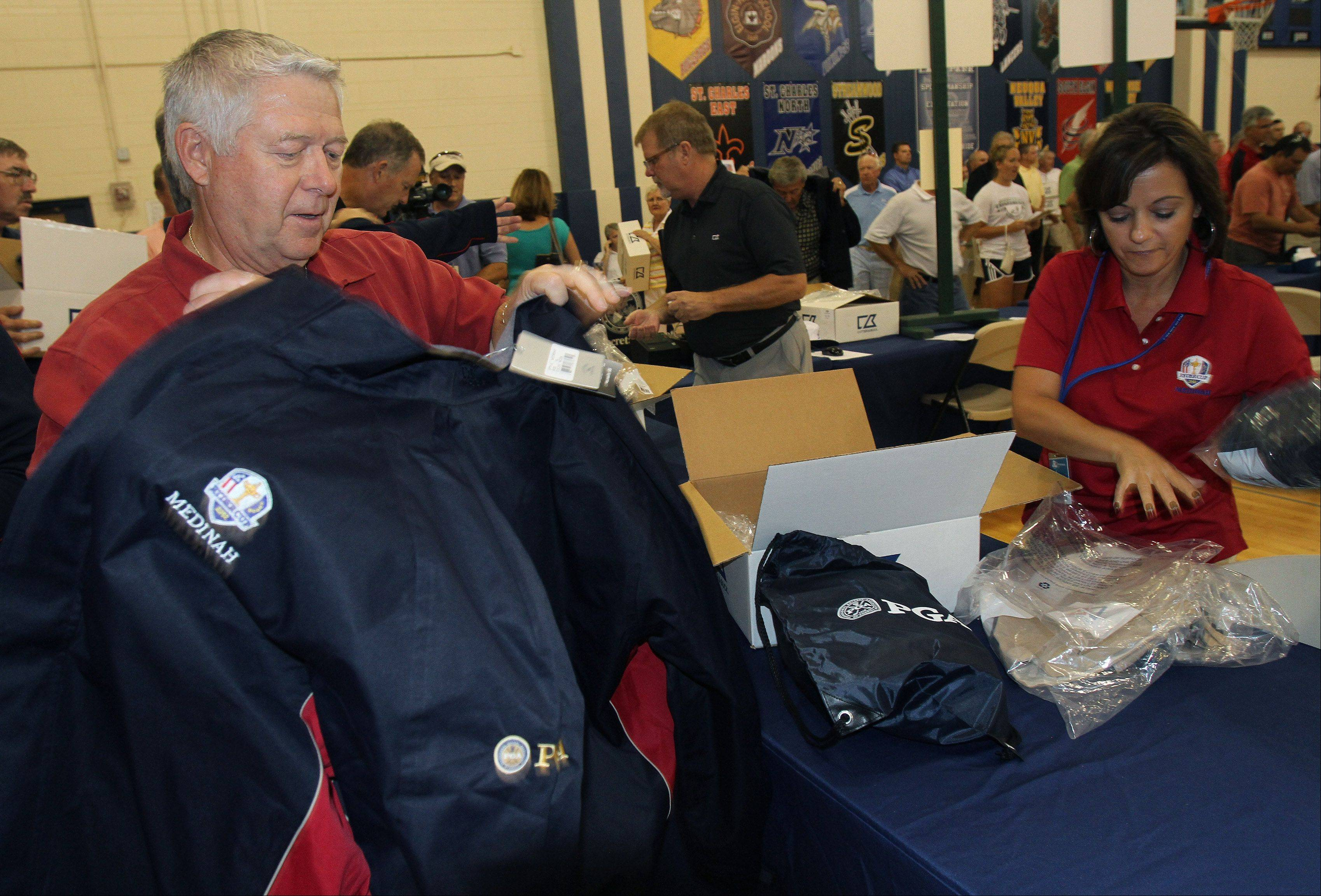 John Gramlich of Glen Ellyn tries on a Ryder Cup volunteer jacket as Sharon Salamone helps him.