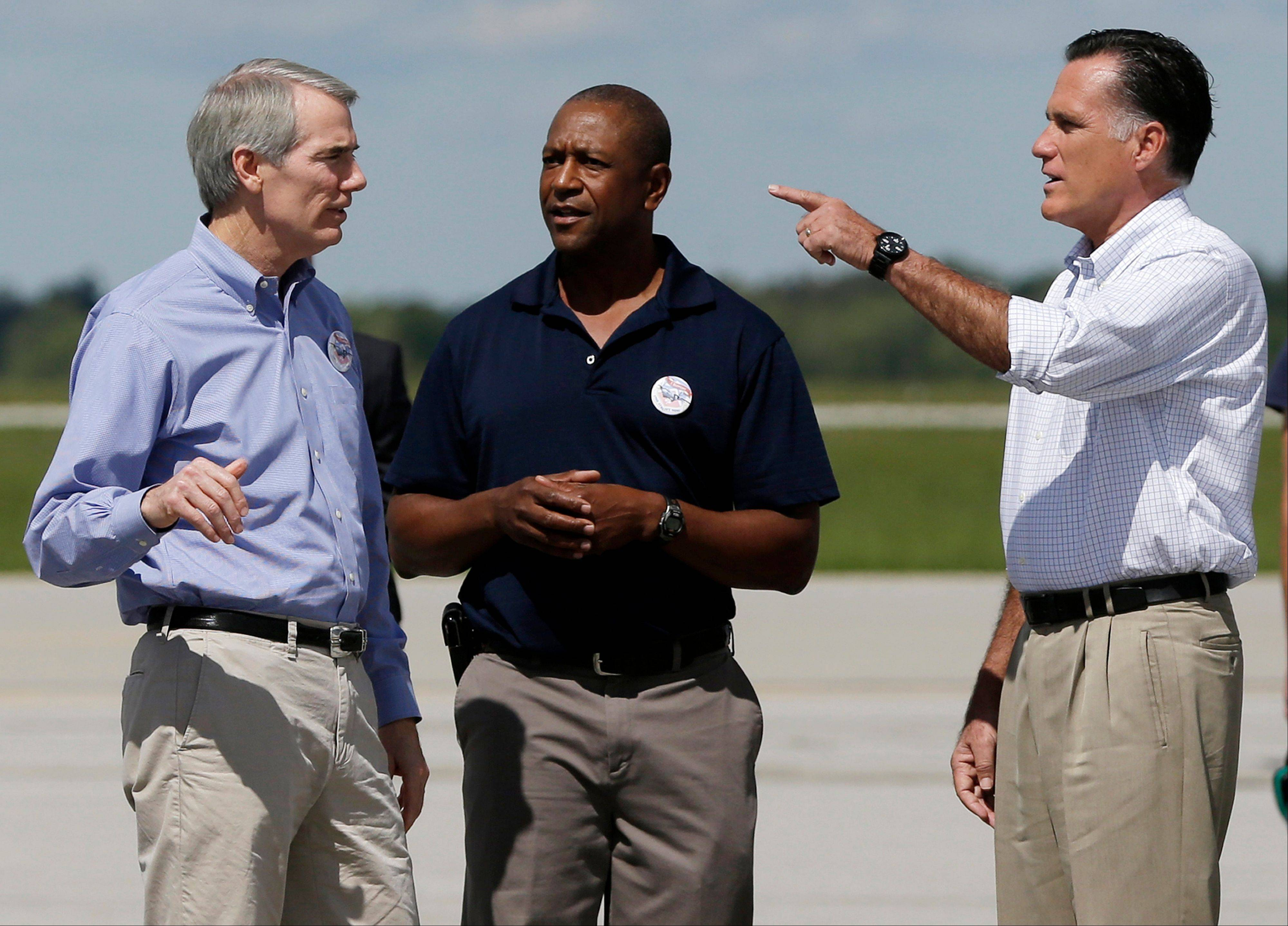 Republican presidential candidate Mitt Romney and Sen. Rob Portman, an Ohio Republican, left, meet with Col. Mike Howard, center, as they arrive at Mansfield Lahm Air National Guard Base in Mansfield, Ohio, Monday.