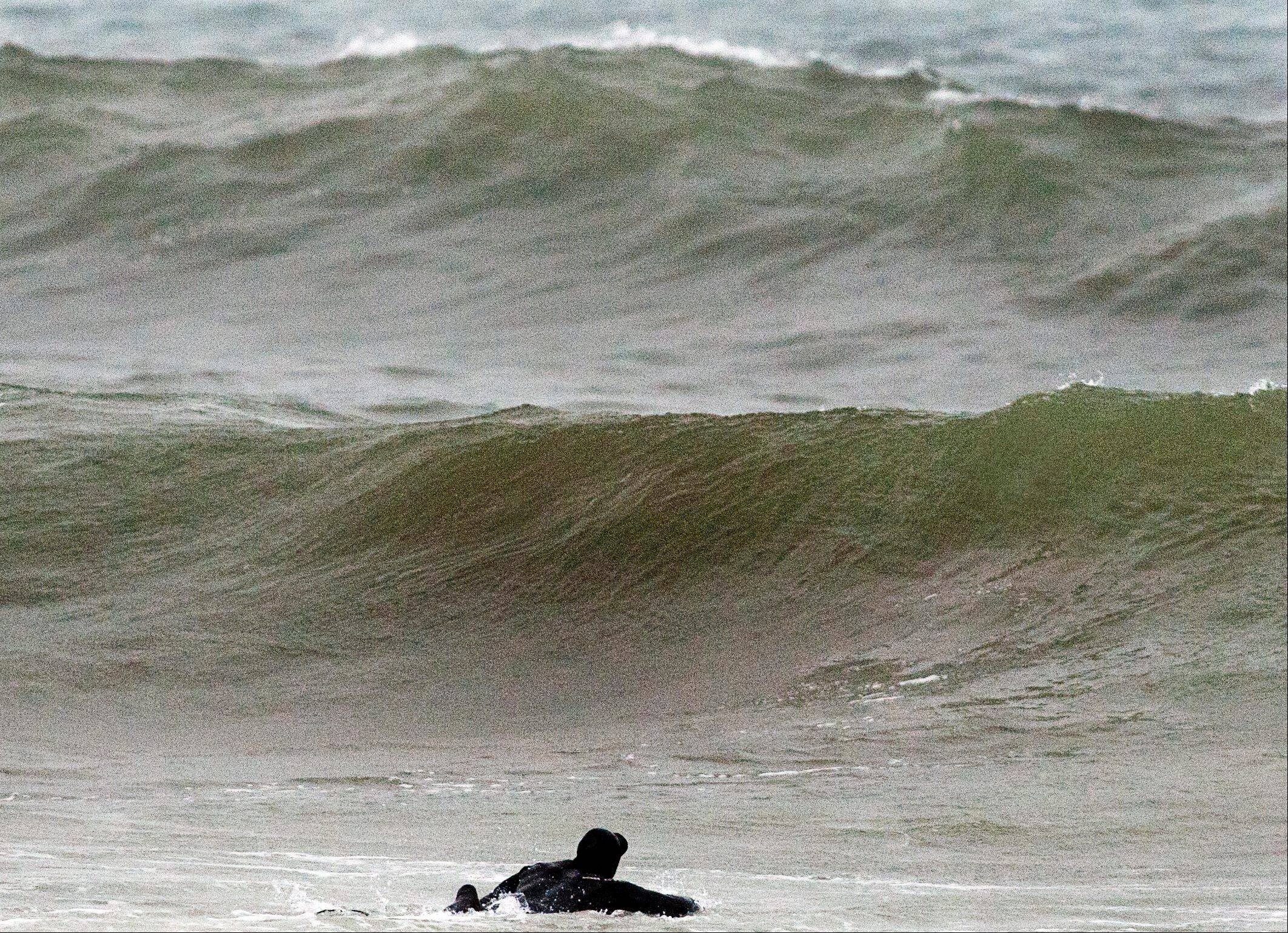 A surfer paddles out into waves generated by Tropical Storm Leslie, at Lawrencetown Beach near Halifax, Nova Scotia, Sunday. Leslie is expected to make landfall in Newfoundland early in the week bringing heavy rain and high winds.
