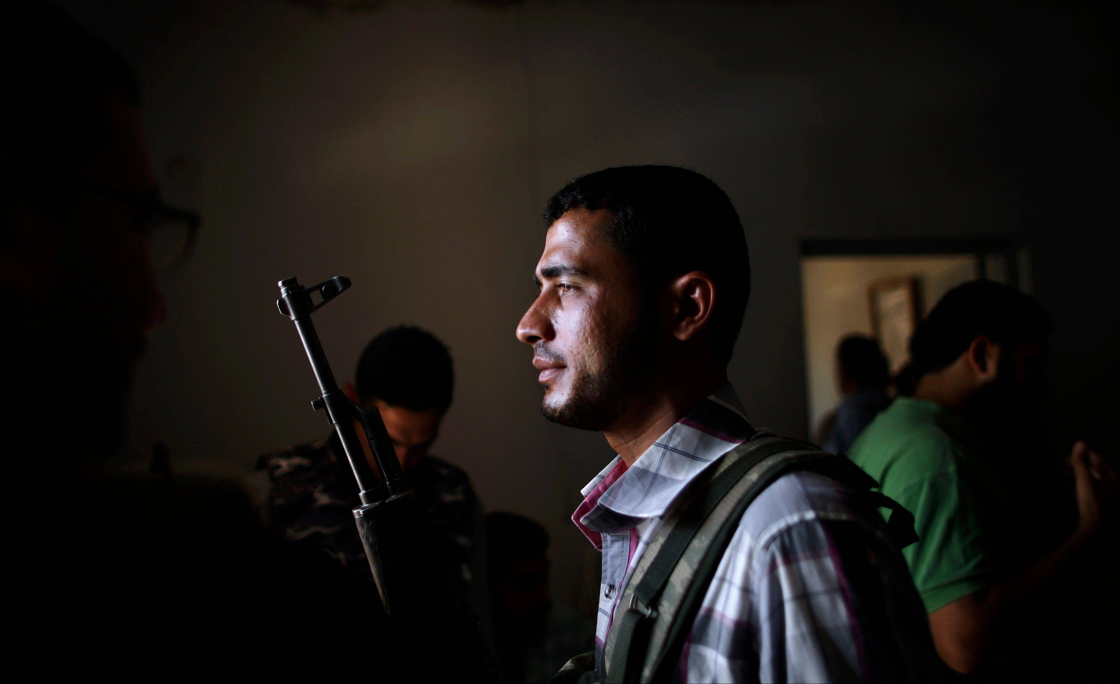A Syrian rebel fighter holds his rifle as he and other fighters head to Aleppo, Syria, to fight government forces Monday.