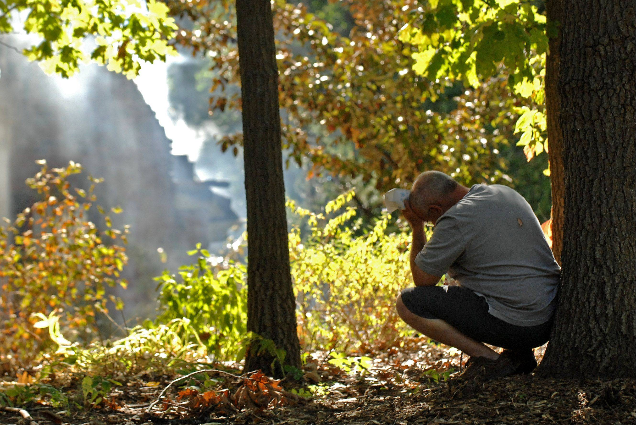 Homeowner Bob Notaro sits by the remains of his house after a fire Monday morning on Spring Wood Lane in Campton Hills.