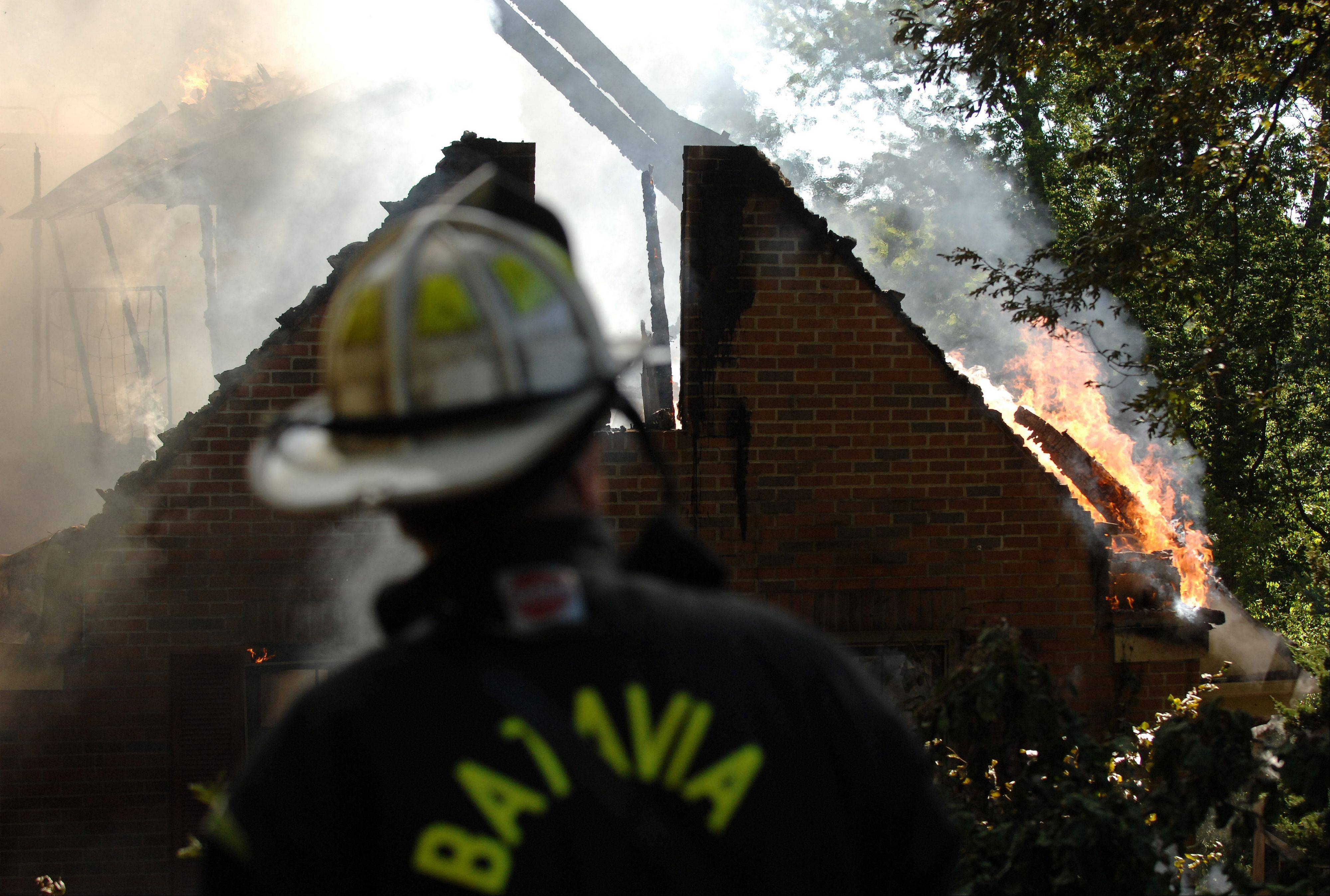 A Batavia firefighter works the scene of Monday's house fire.