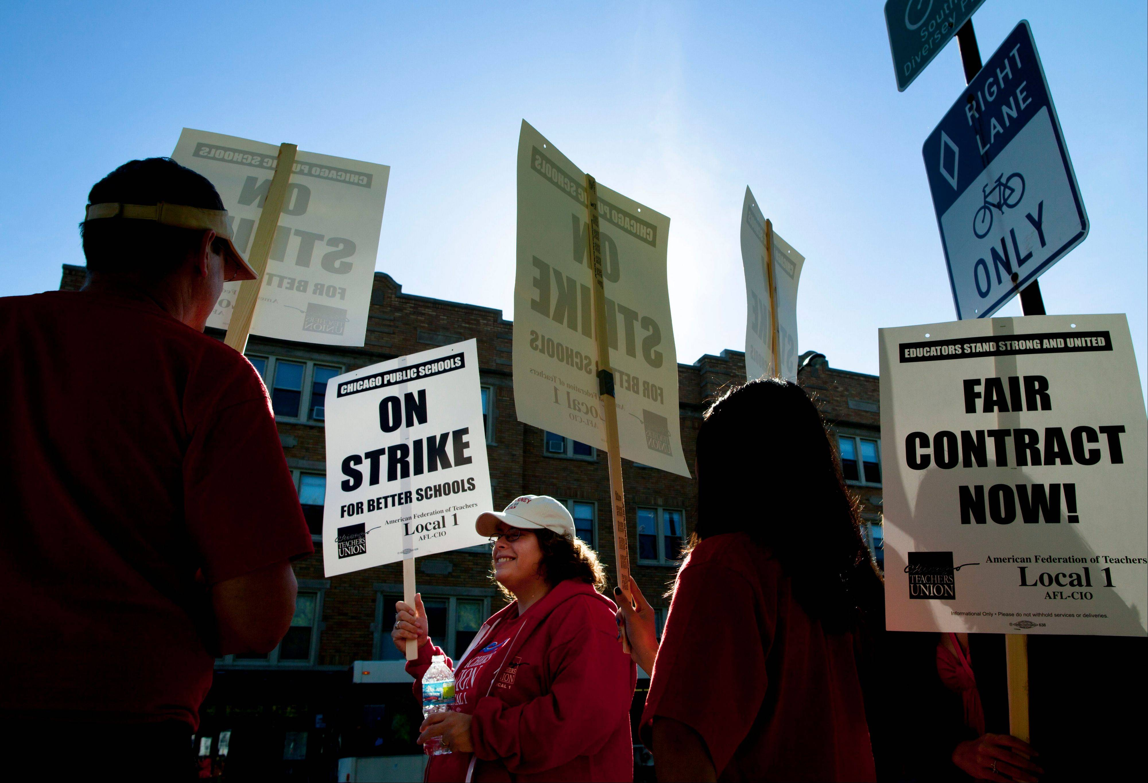 "Public school teachers picket outside Amundsen High School in Chicago on the first day of a strike by the Chicago Teachers Union Monday. The school is one of more than 140 schools in the Chicago Public Schools' ""Children First"" contingency plan, which feeds and houses students for four hours during the strike."
