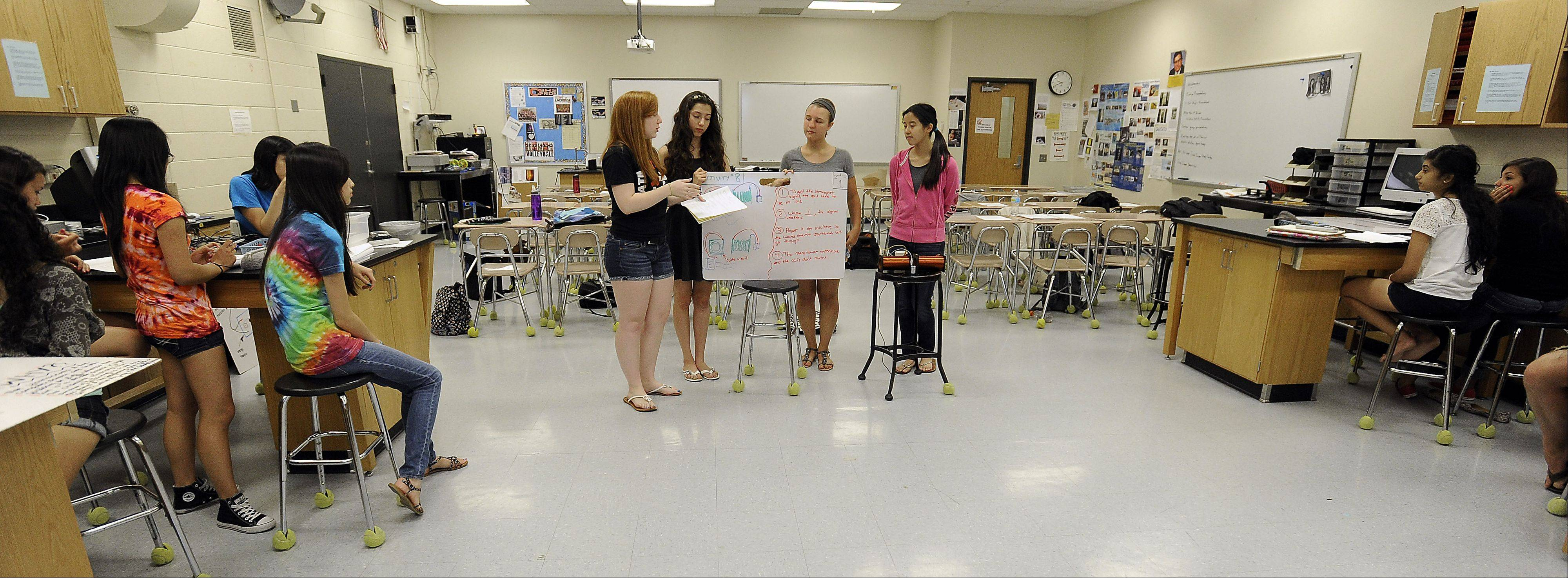 In a predominantly female physics class at Barrington High School, Courtney Wilt, 16, of Inverness, Karen Rojas, 16, of Carpentersville, Leah Thomas, 16, of Barrington and Jenny Vu, 16, of Barrington explain their physics project to the rest of their classmates during summer school.