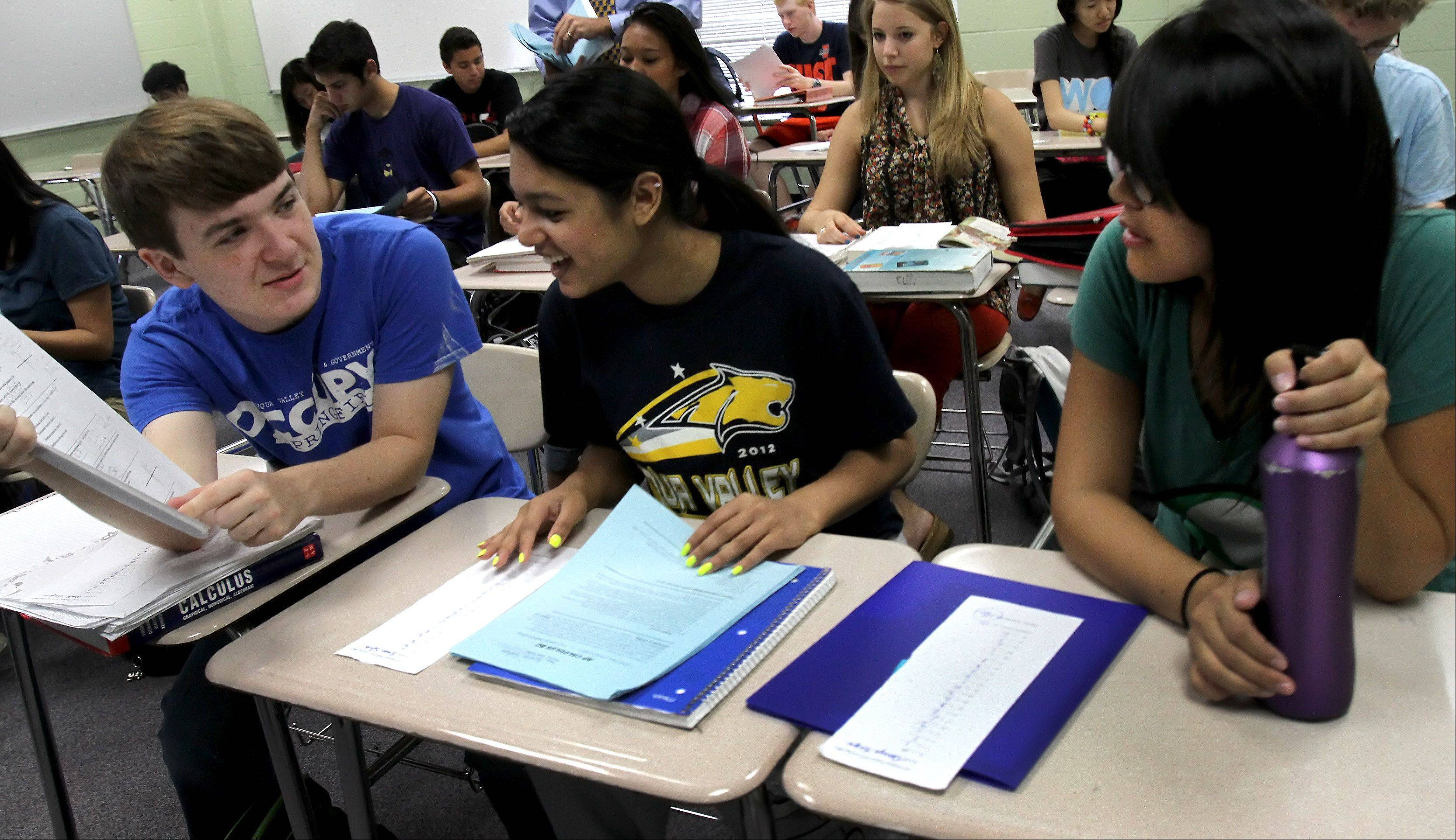 Mark Gaughan, left, a senior, Simron Sahoo, a junior, and Danaya Siripun, a senior, look over test results in an Advanced Placement calculus class at Neuqua Valley High School in Naperville.