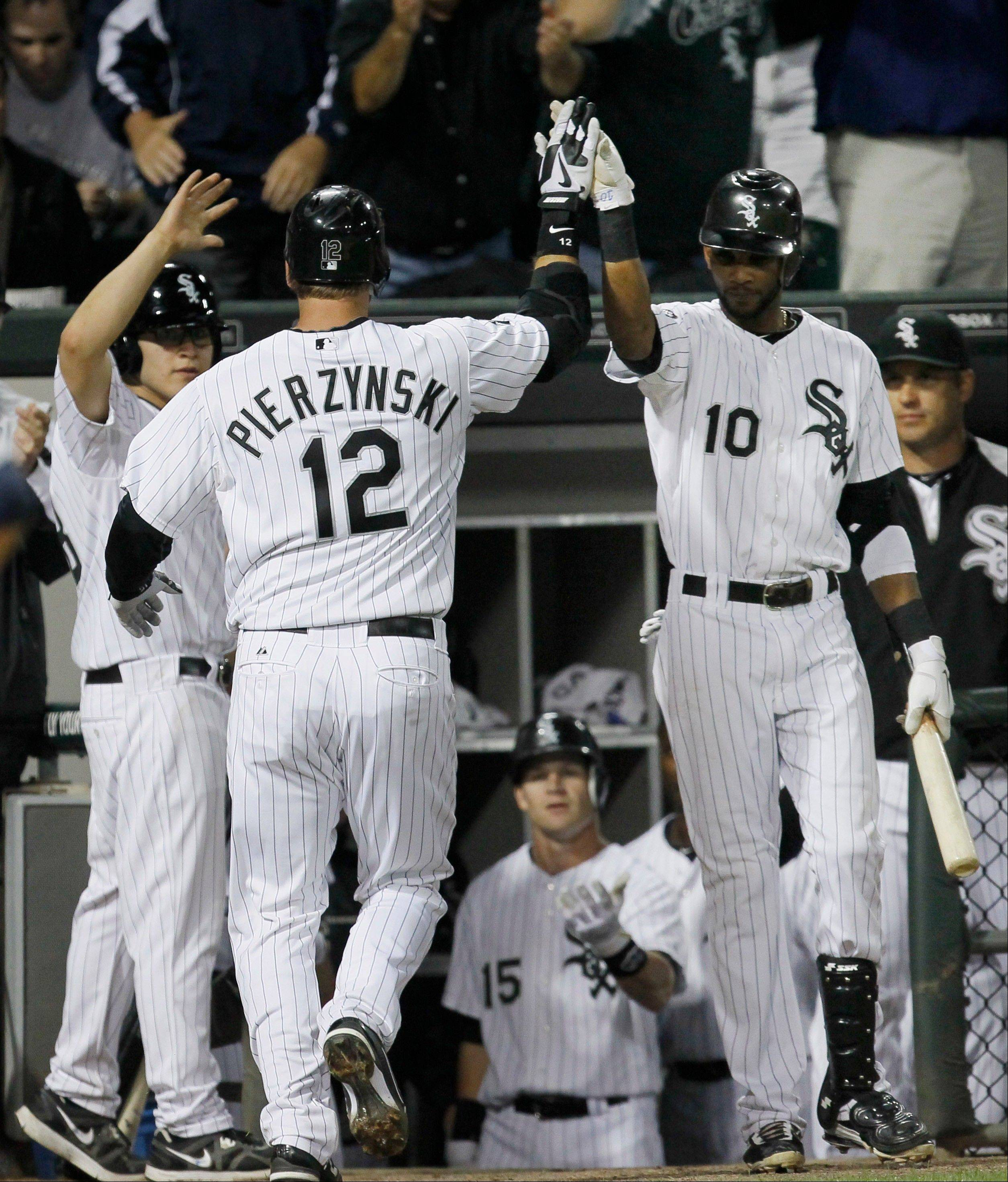 White Sox catcher A.J. Pierzynski is greeted outside the dugout by the bat boy, left, and Alexei Ramirez after hitting a home run off Detroit Tigers starting pitcher Rick Porcello during Monday's sixth inning at U.S. Cellular Field.