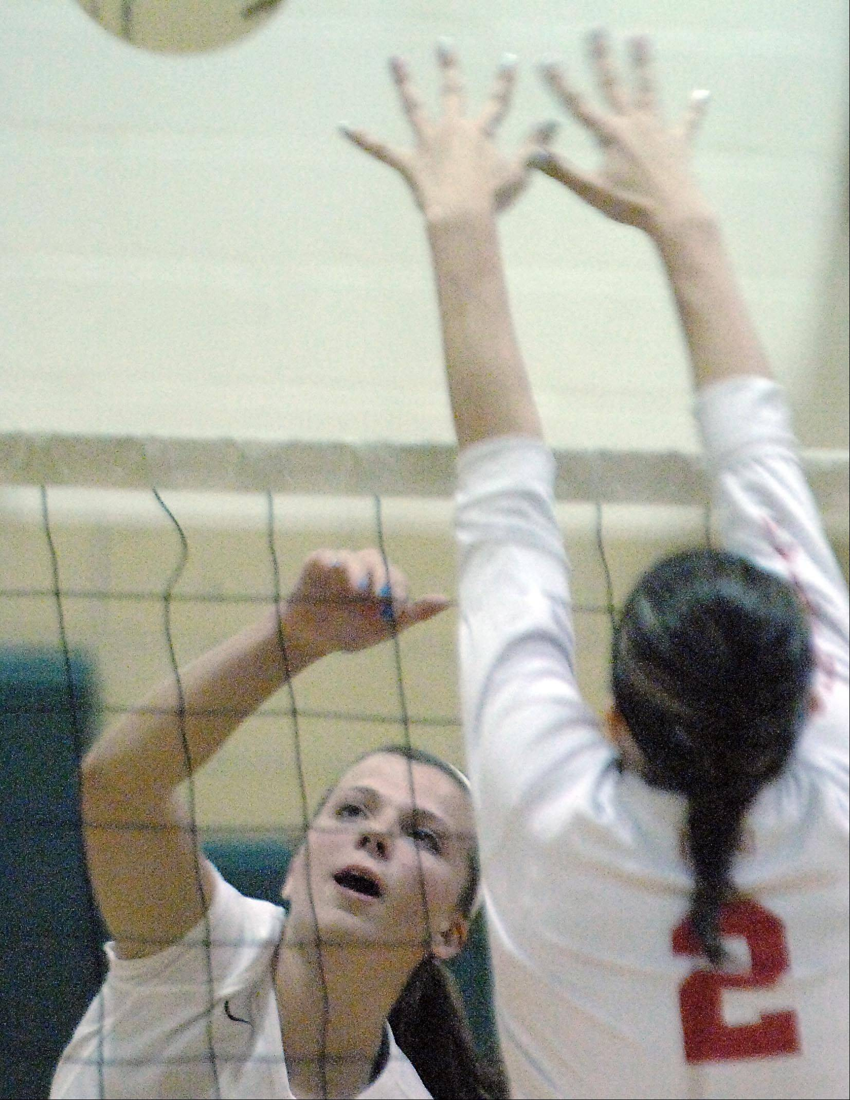 St. Edward's Katie Swanson hits past Aurora Christian's Faith Montalbano Monday in Elgin.
