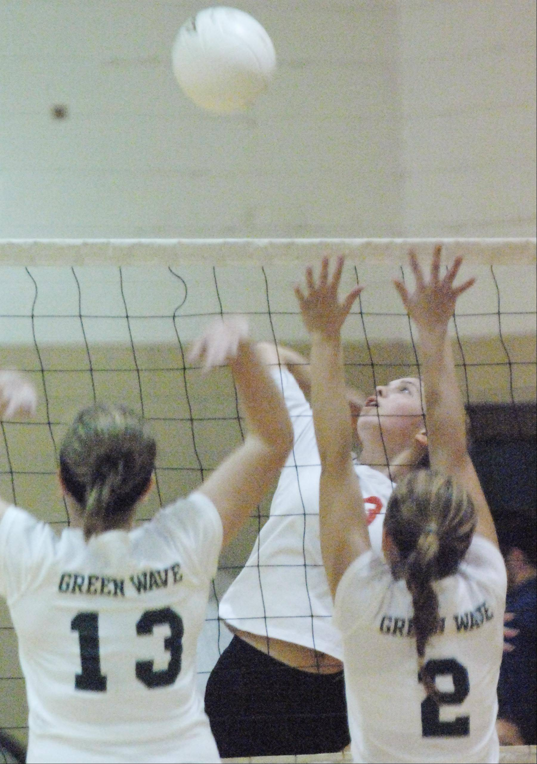 St. Edward's Cory Kelly and Mallory Gross, right, jump to block Aurora Christian's Jamie Gebauer Monday in Elgin.