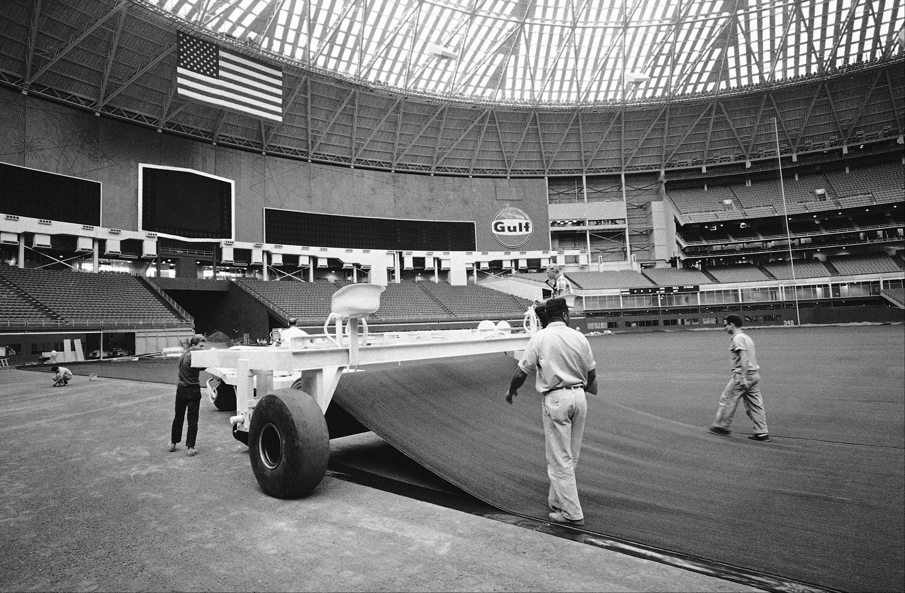 The Astrodome in Houston, Texas is the world?s first covered baseball stadium. It keeps out the rain, the wind, the sleet, the snow and it also keeps out the sun. Because of the last attribute the grass doesn?t grow well at the Astrodome, so it?s being replaced. In its place ?Astroturf? is being installed. Astroturf is a green synthetic nylon that is installed like a wall-to-wall-carpet in strips 14-feet wide and costs $2.00 per square feet. When the old cry of ?play ball? is heard the Astroturf is all zipped together and the fielders can chase fly balls all day without the slightest fear of stepping in a gopher hole. Workmen zipper up the Astroturf carpet completely covered the outfield, workers spread the warning track gravel along the fence in Houston on July 25, 1966.
