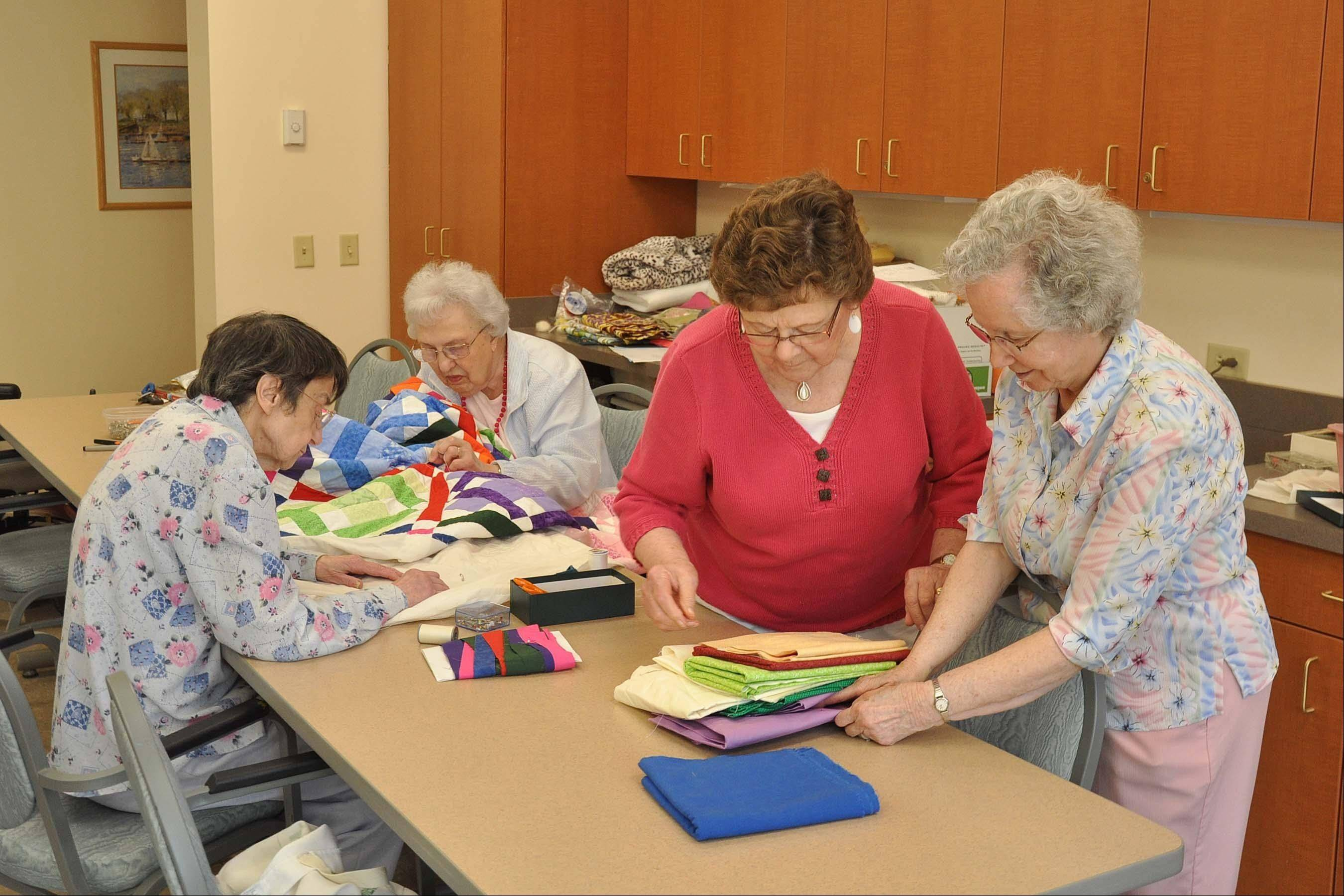Helen Hitt, Eileen Waldron, Shirley Adair and Marilyn Albright sew pieces for the 2012 Holmstad Bazaar quilt. The annual show will be Sept. 29.