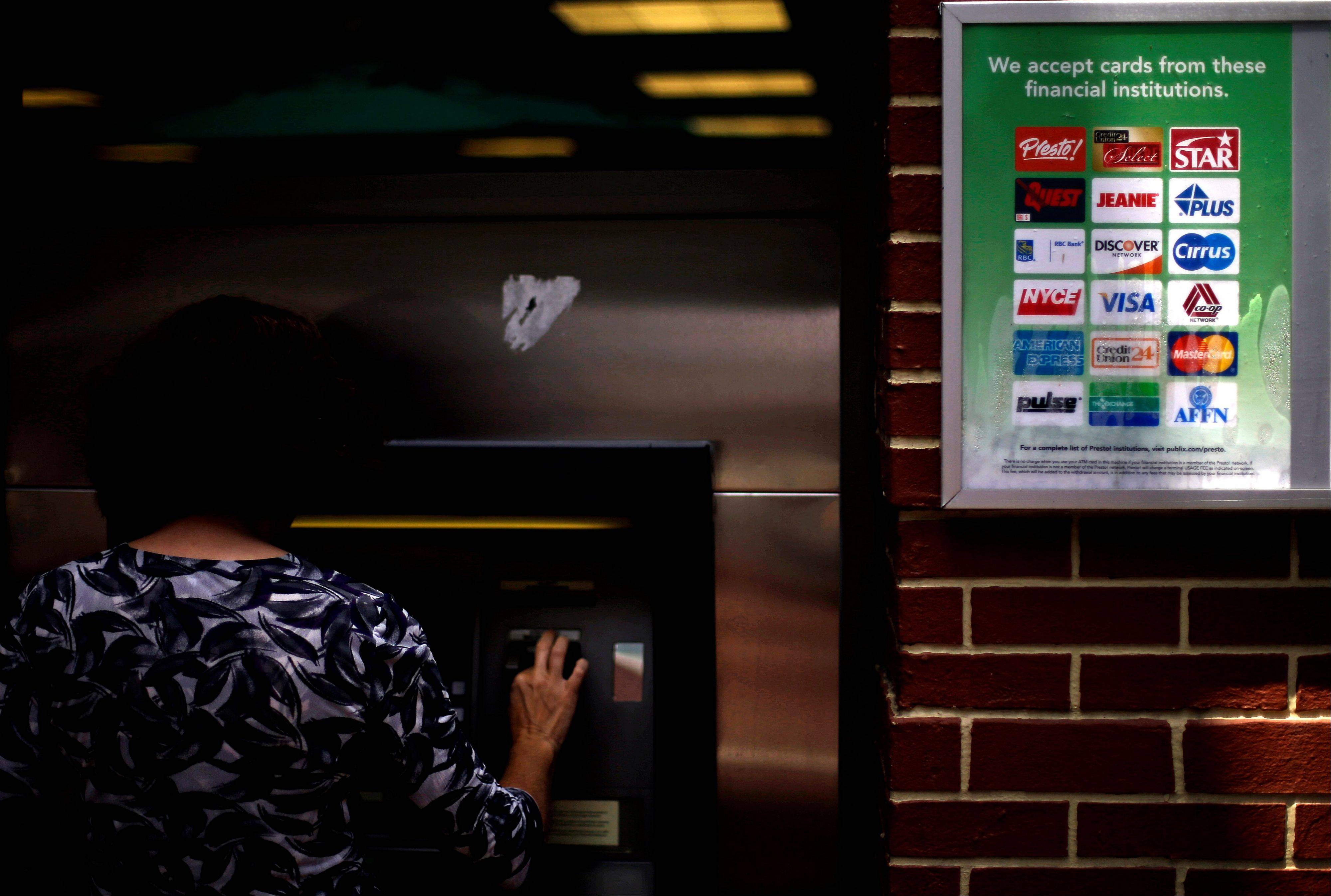 Associated Press/July 16, 2012 Credit logos are seen as a consumer withdraws money from an ATM in Atlanta.