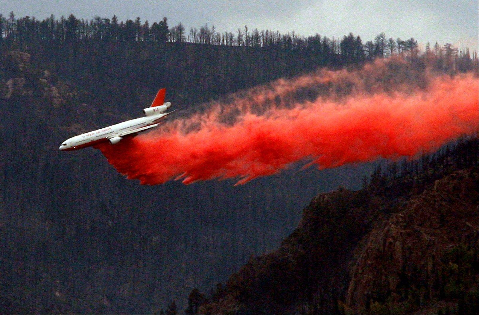 A DC-10 tanker jet drops a load of fire retardant on the north side of Casper Mountain as a wildfire continues to burn Tuesday in Wyoming. The fire was listed at more than 15,000 acres as of Tuesday morning.