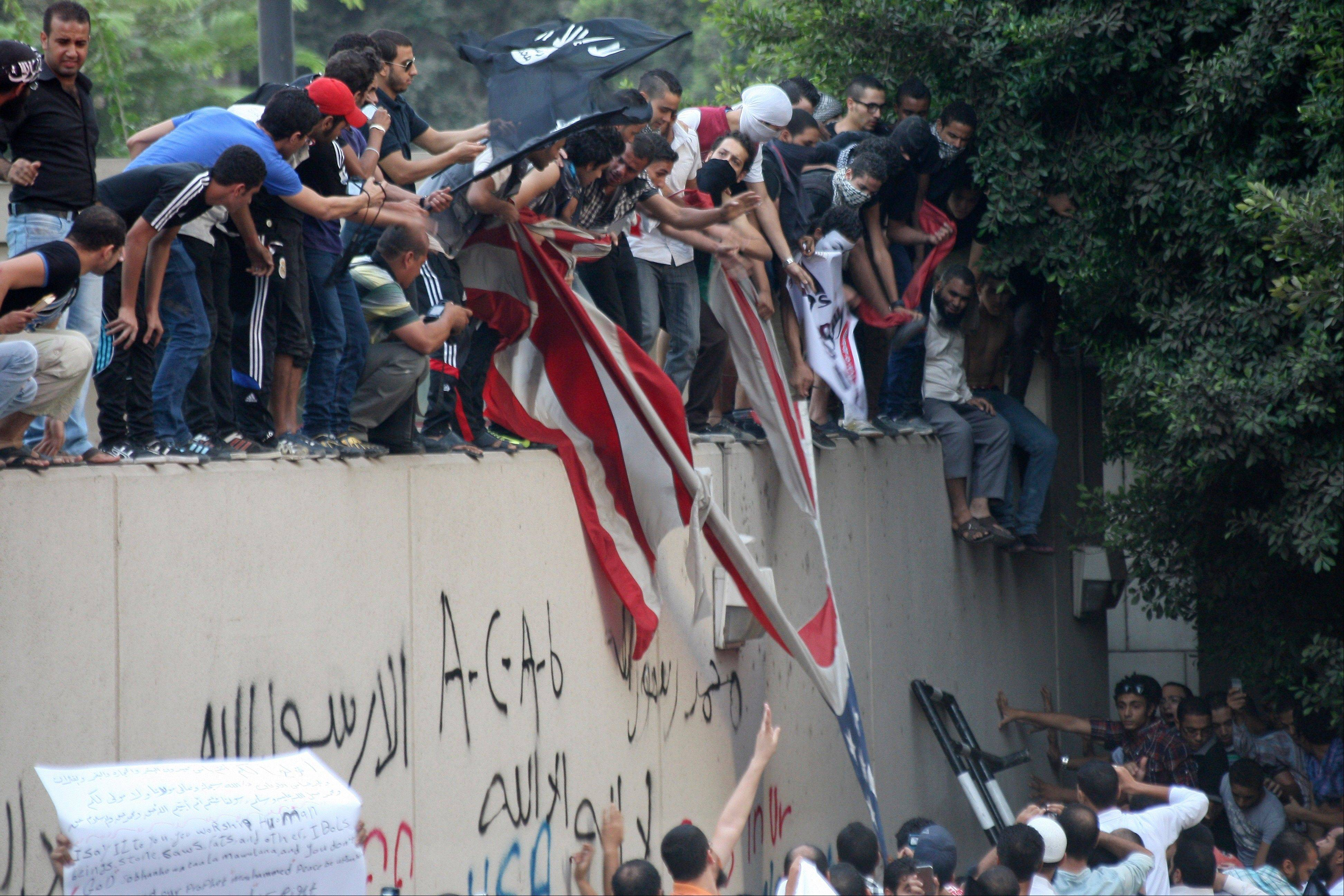 Protesters destroy an American flag pulled down Tuesday from the U.S. embassy in Cairo, Egypt.
