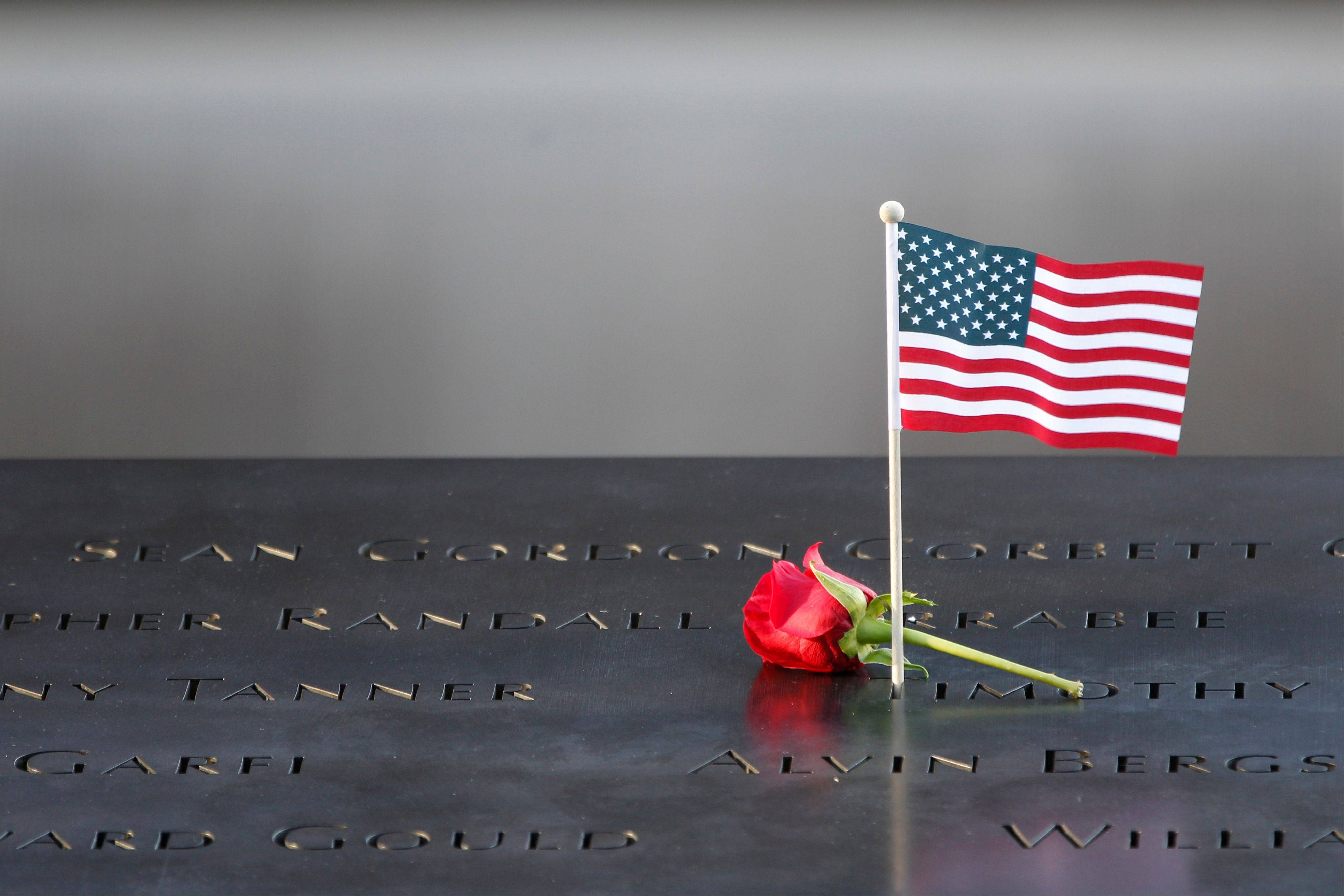 A flower and an American flag are placed next to the names inscribed on the edge of one of the World Trade Center Memorial reflecting pools, during the observance held on the 11th anniversary of the attacks on the World Trade Center, Tuesday, Sept. 11, 2012 in New York.