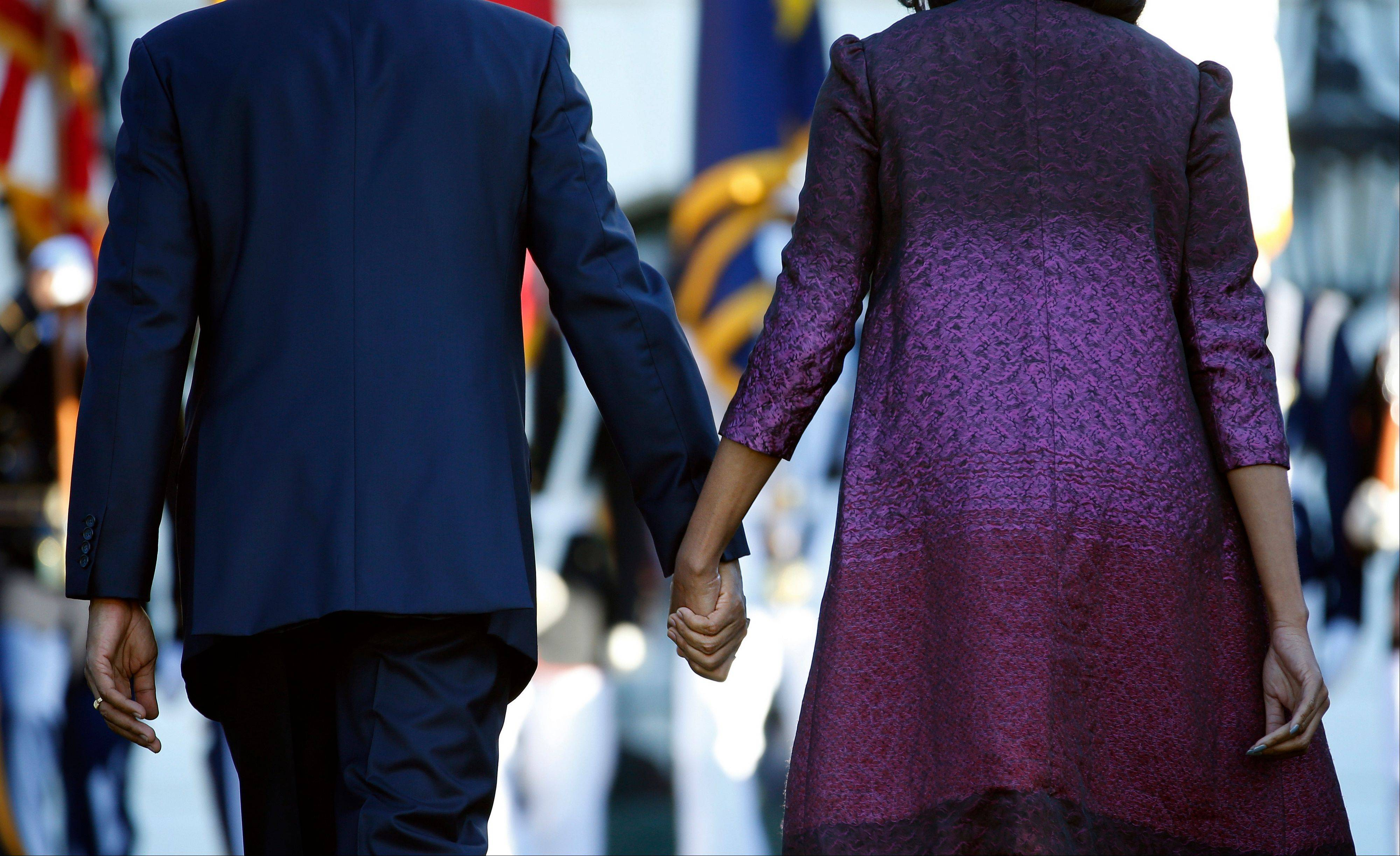 President Barack Obama and first lady Michelle Obama hold hands as they walk back to the White House in Washington, Tuesday, Sept. 11, 2012, after joining members of the White House staff during a moment of silence to mark the 11th anniversary of the Sept, 11th.