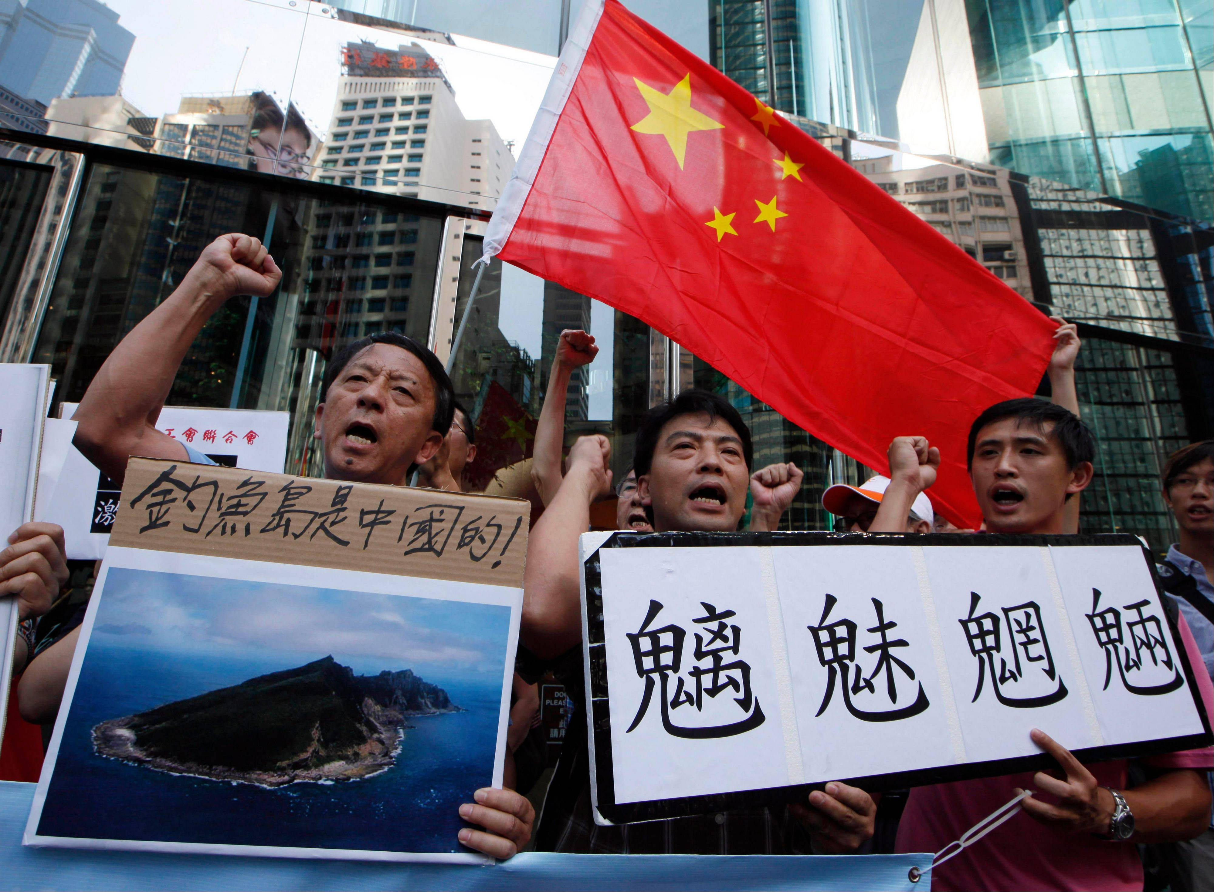"Protesters demonstrating against Japan's claim to disputed islands chant slogans as they hold a picture of the rocky islands, known as Diaoyu to Chinese and Senkaku to Japanese, reading ""Diaoyu belongs to China"" as others carry a Chinese national flag and a sign reading ""evil spirits of mountains and rivers"" during a rally outside the Japanese Consulate General in Hong Kong Tuesday, Sept. 11, 2012."
