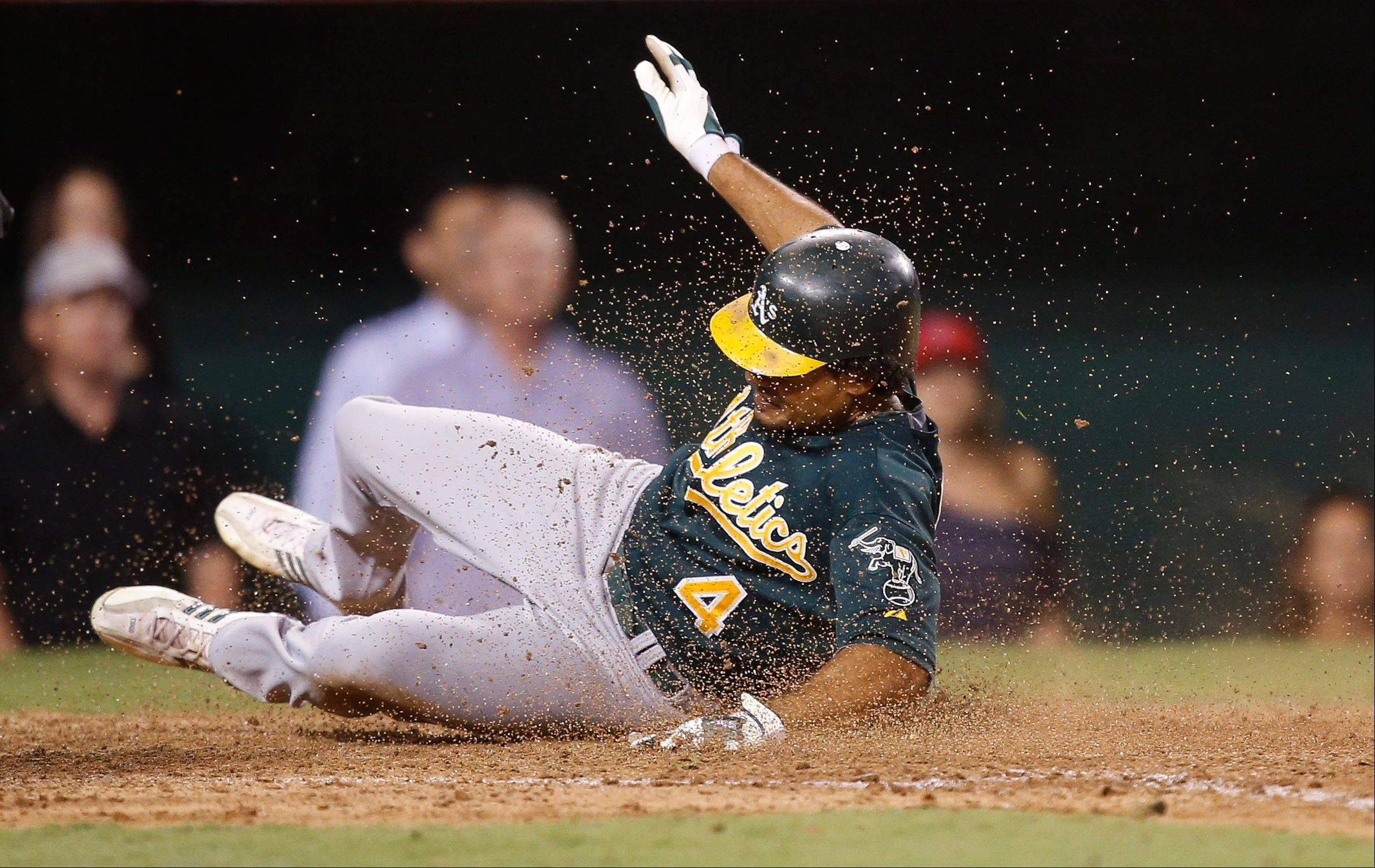 Oakland's Coco Crisp scores on a fielding error by Los Angeles Angels right fielder Torii Hunter in the ninth inning Tuesday in Anaheim, Calif.