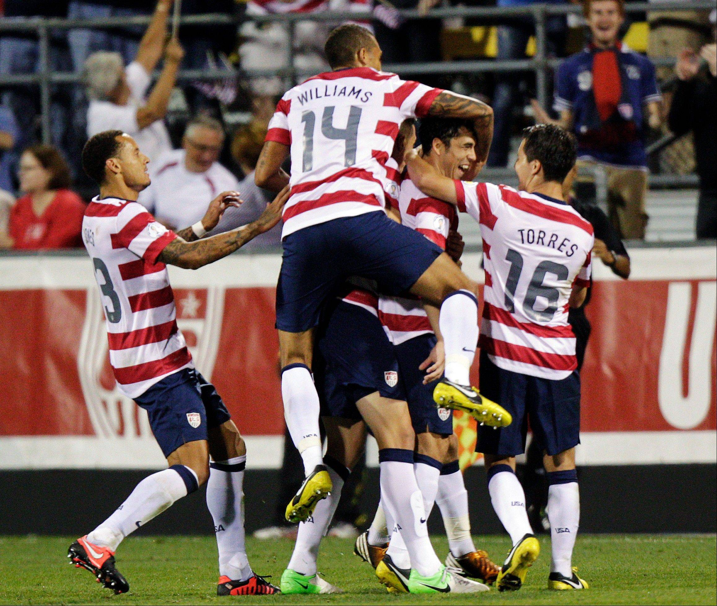United States players celebrate a goal by Herculez Gomez against Jamaica during the second half of a World Cup qualifying soccer match Tuesday in Columbus, Ohio.