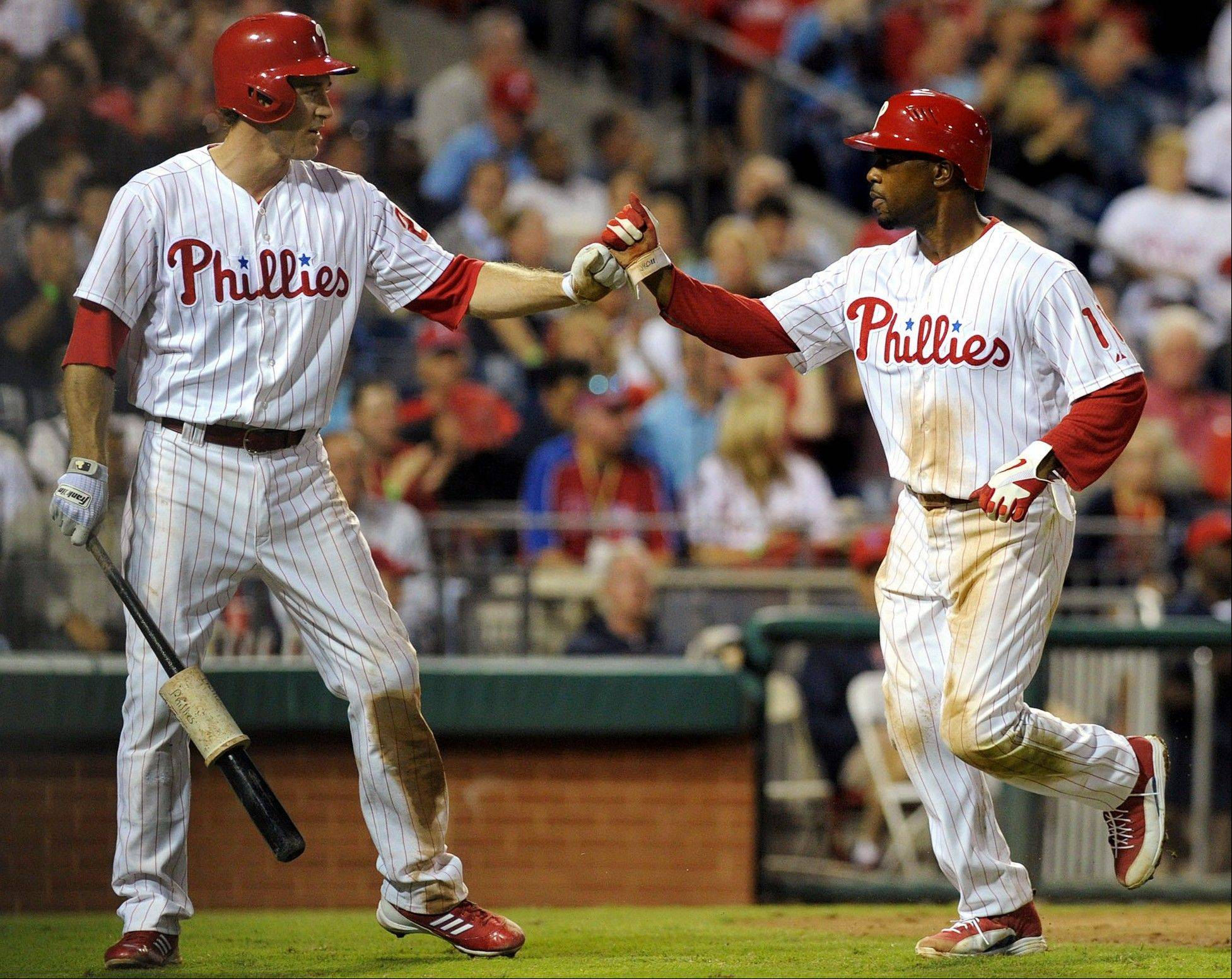 Philadelphia's Chase Utley, left, greets Jimmy Rollins as he crosses the plate to score on a ground ball from Juan Pierre in the fifth inning Tuesday at home against Miami.