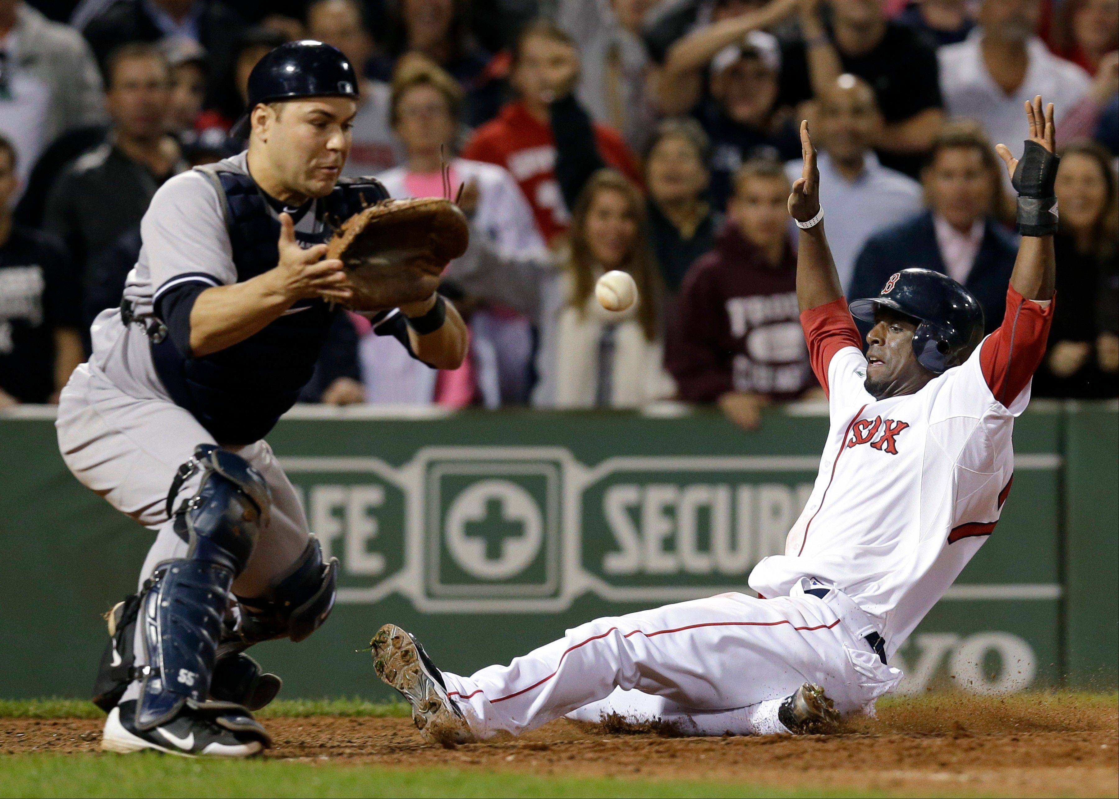 Boston's Pedro Ciriaco slides in to score the winning run on a single hit by Jacoby Ellsbury as New York Yankees catcher Russell Martin waits for the late throw Tuesday at Fenway Park.