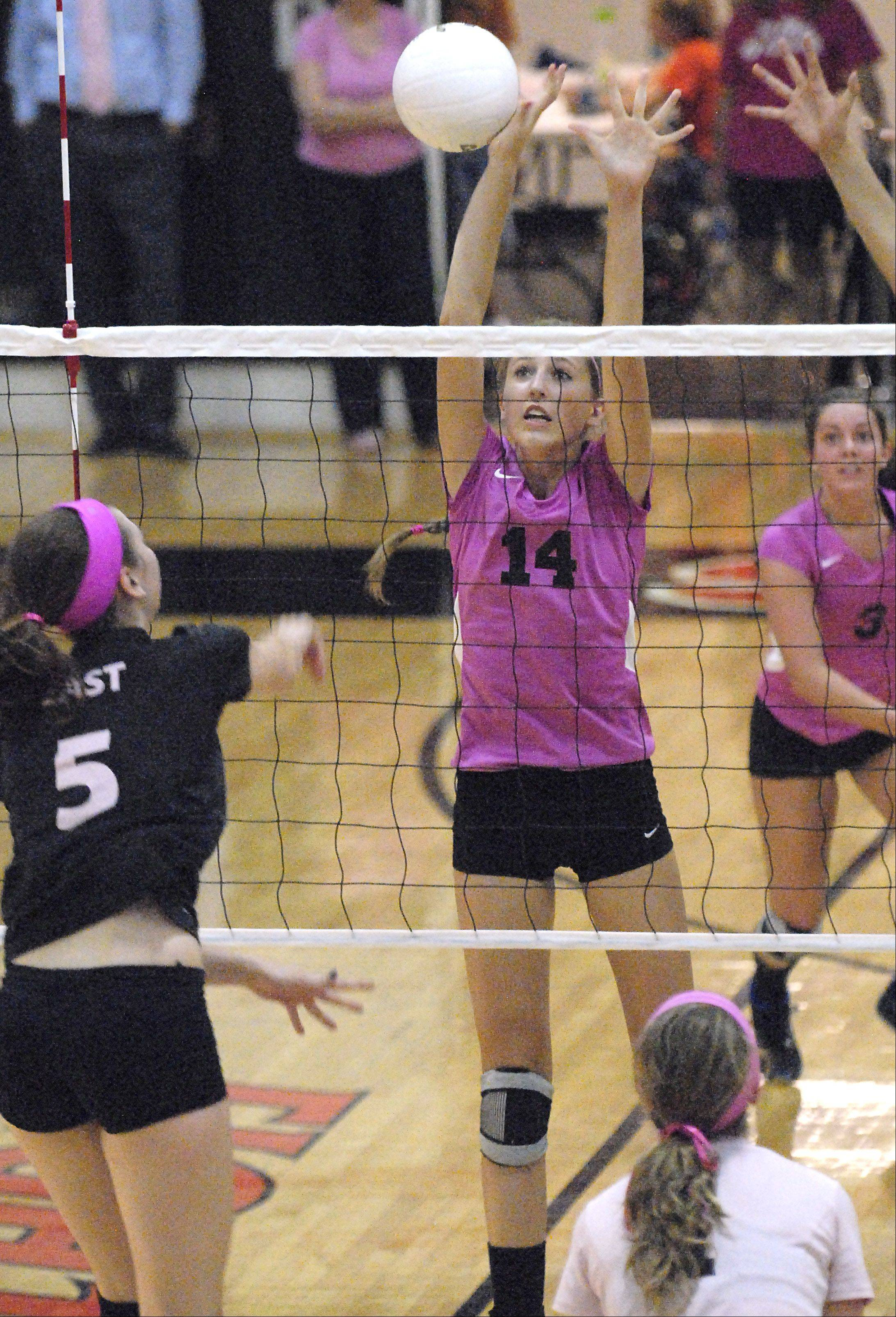 St. Charles North's Emily Carroll deflects a spike by St. Charles East's Nicole Woods in game one on Tuesday, September 11.