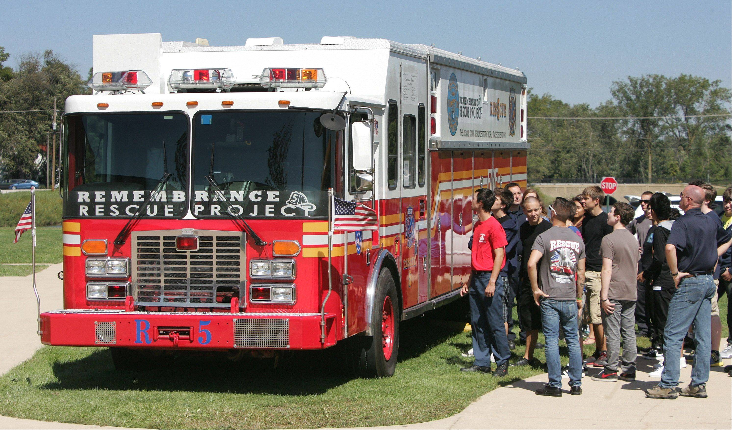 Members of a fire service class look at New York Fire Department Rescue 5 engine on display during the 9/11 Ceremony Tuesday at the Lake County High Schools Technology Campus in Grayslake. The fire truck was on the scene in New York on September 11, 2001- all eleven firefighters with the truck at the time lost their lives. The truck was restored by Remembrance Rescue Project.