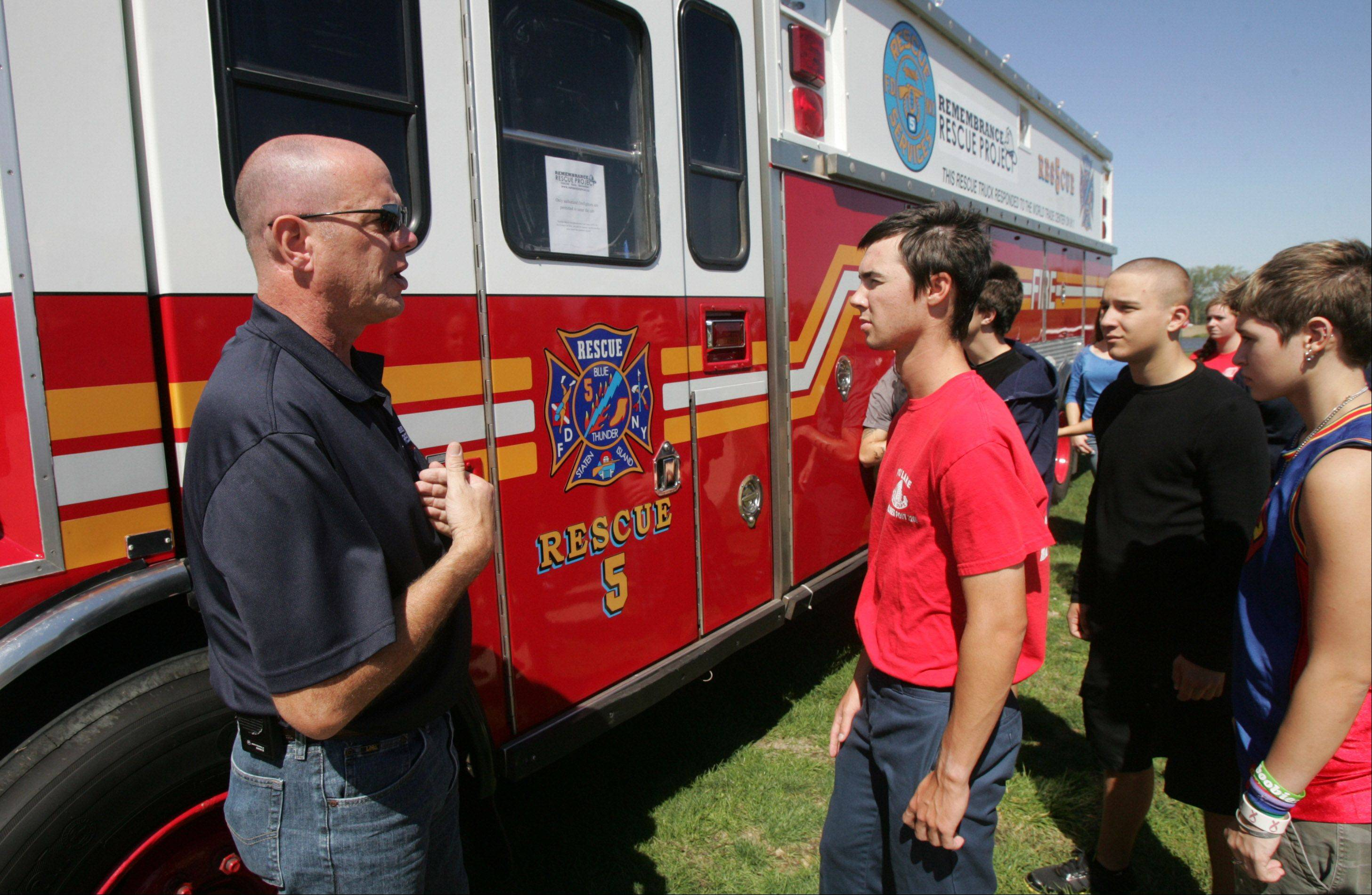 Scott Vaughn of Remembrance Rescue Project talks to a fire service class about the New York Fire Department Rescue 5 engine on display during the 9/11 Ceremony Tuesday at the Lake County High Schools Technology Campus in Grayslake.