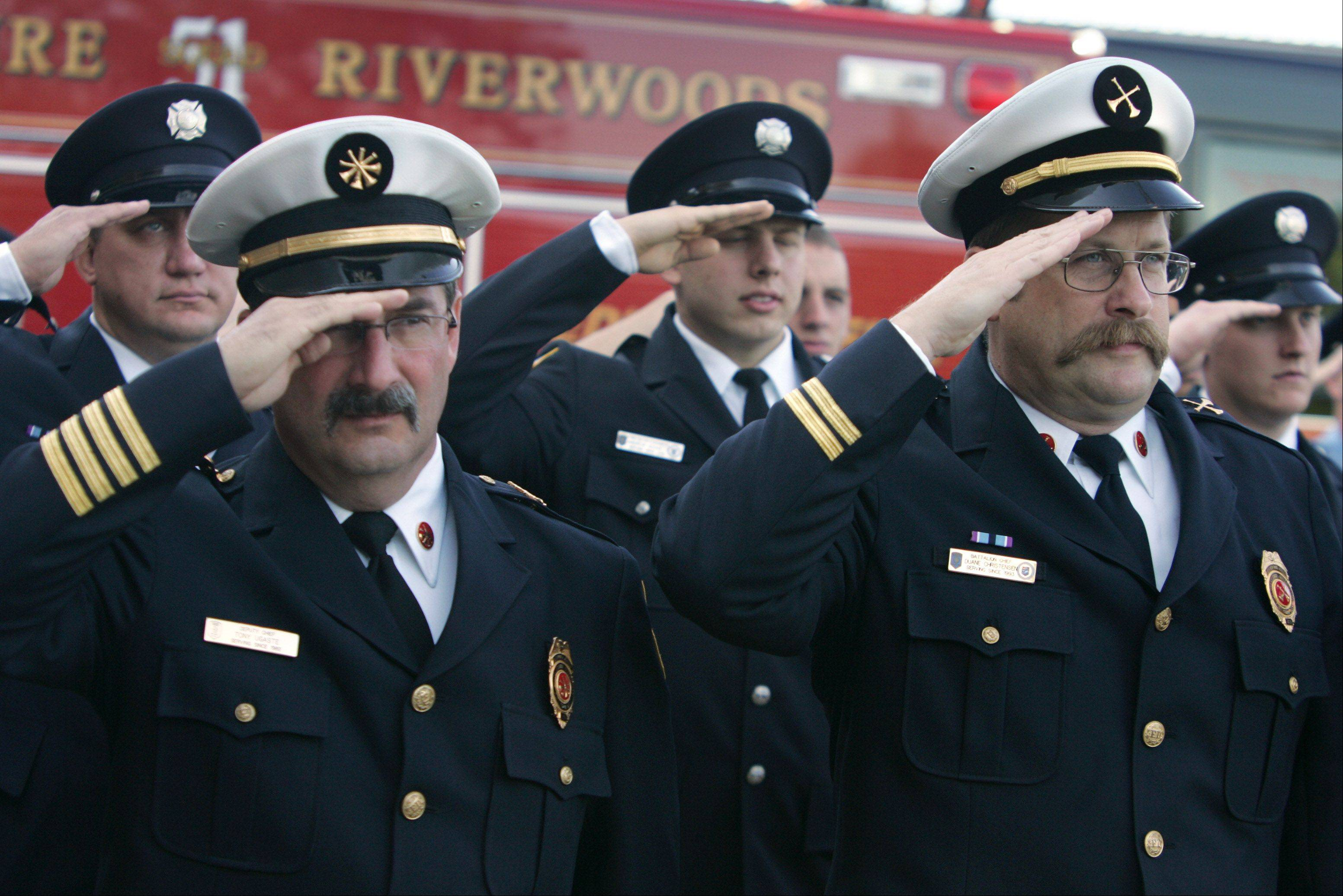 Deputy Chief Tony Ugaste, left, and Battallion Chief Duane Christensen salute during the raising of the flag at the Remember 9-1-1 Ceremony by the Lincolnshire-Riverwoods Fire Protection District Tuesday at the Schelter Road fire station.