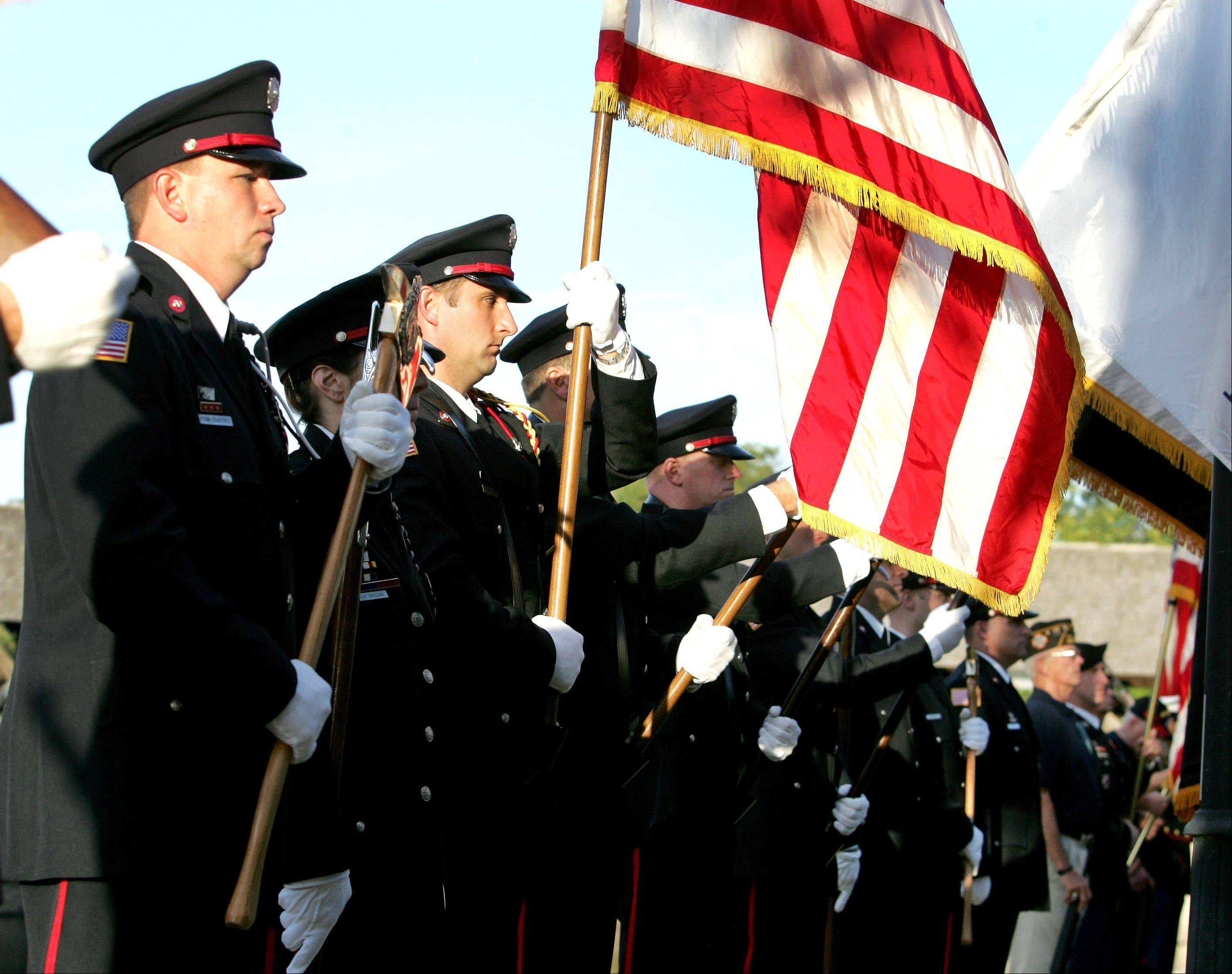 A combined color guard of the Naperville Fire and Police departments, American Legion Post 43 and the Veterans of Foreign Wars Post 3873, present colors for the annual September 11 remembrance at the Cmdr. Dan Shanower Memorial in Naperville on Tuesday.
