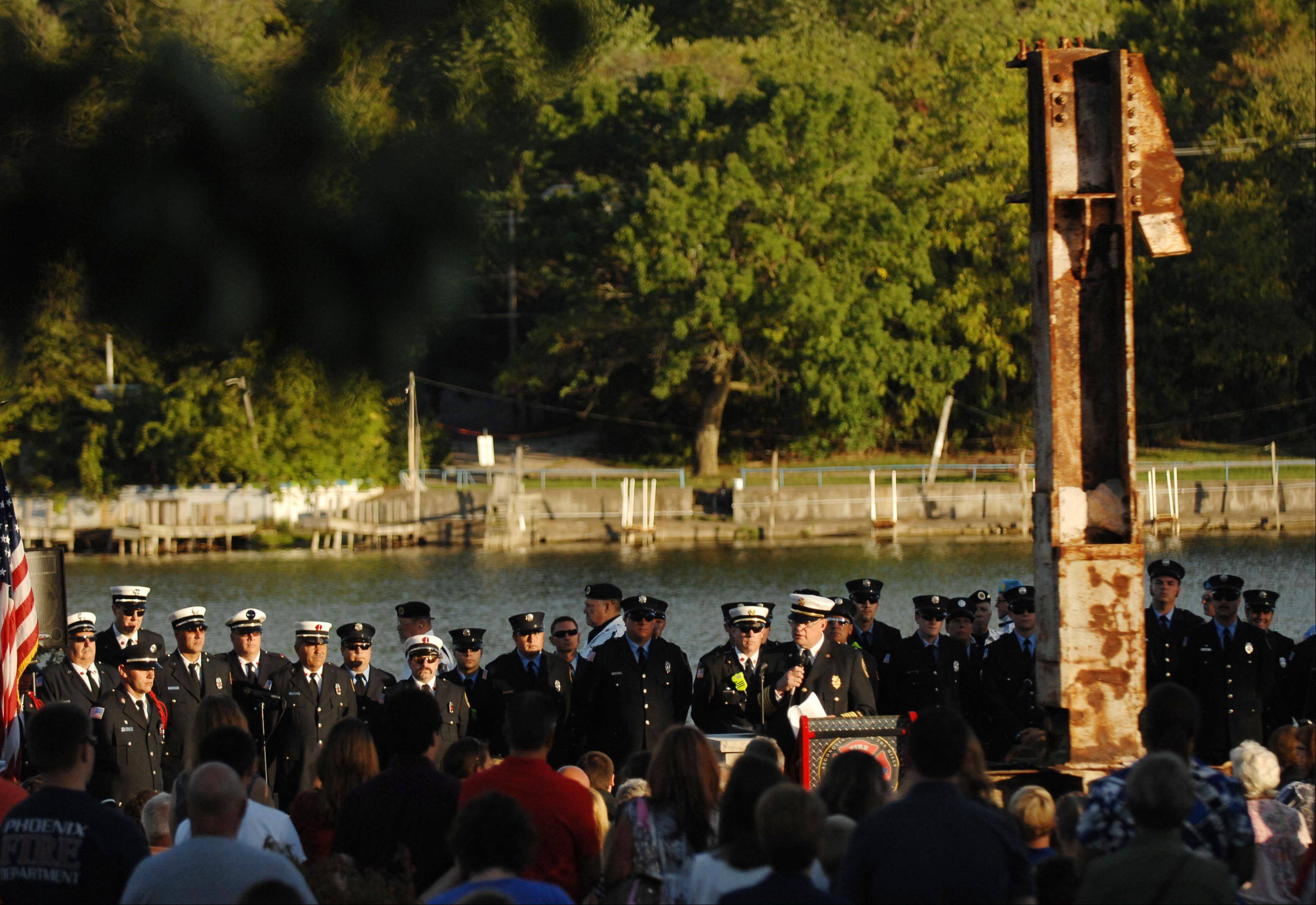 Chief Kevin Rynders of the Algonquin-Lake in the Hills Fire Protection District speaks to the crowd on the shore of the Fox River Tuesday in Algonquin during a Firefighter Memorial Dedication of a 5,000 pound iron beam from the World Trade Center.
